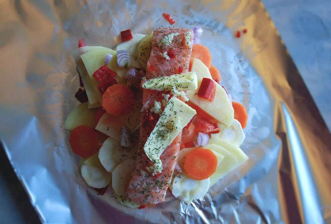 Bare steking gjenstår . Grønnsaker er kuttet i tynne skiver og fisken er lagt oppå. Obs: Her er folien i smaleste laget, så grønnsakene ble fordelt i tre pakker istedenfor to.