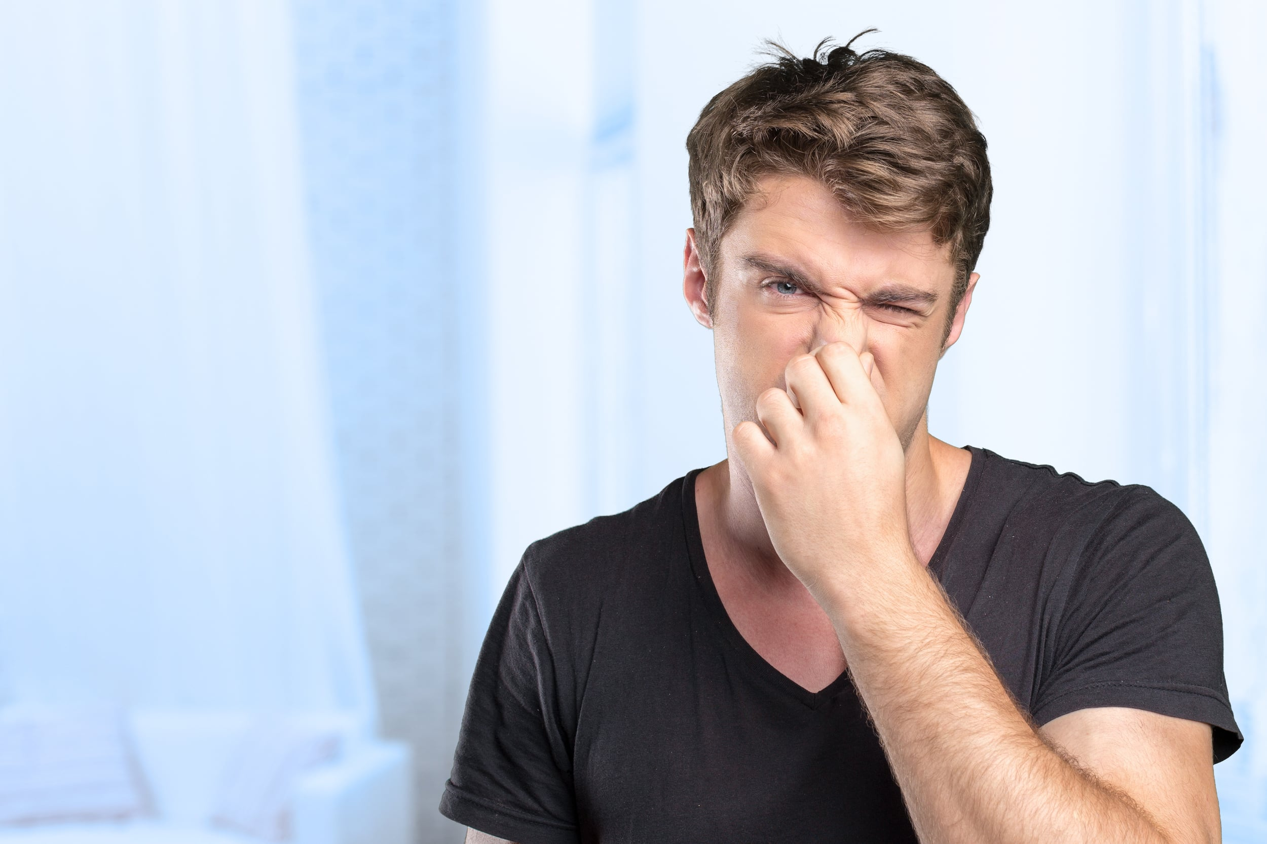 man holding nose due to bad smell in property