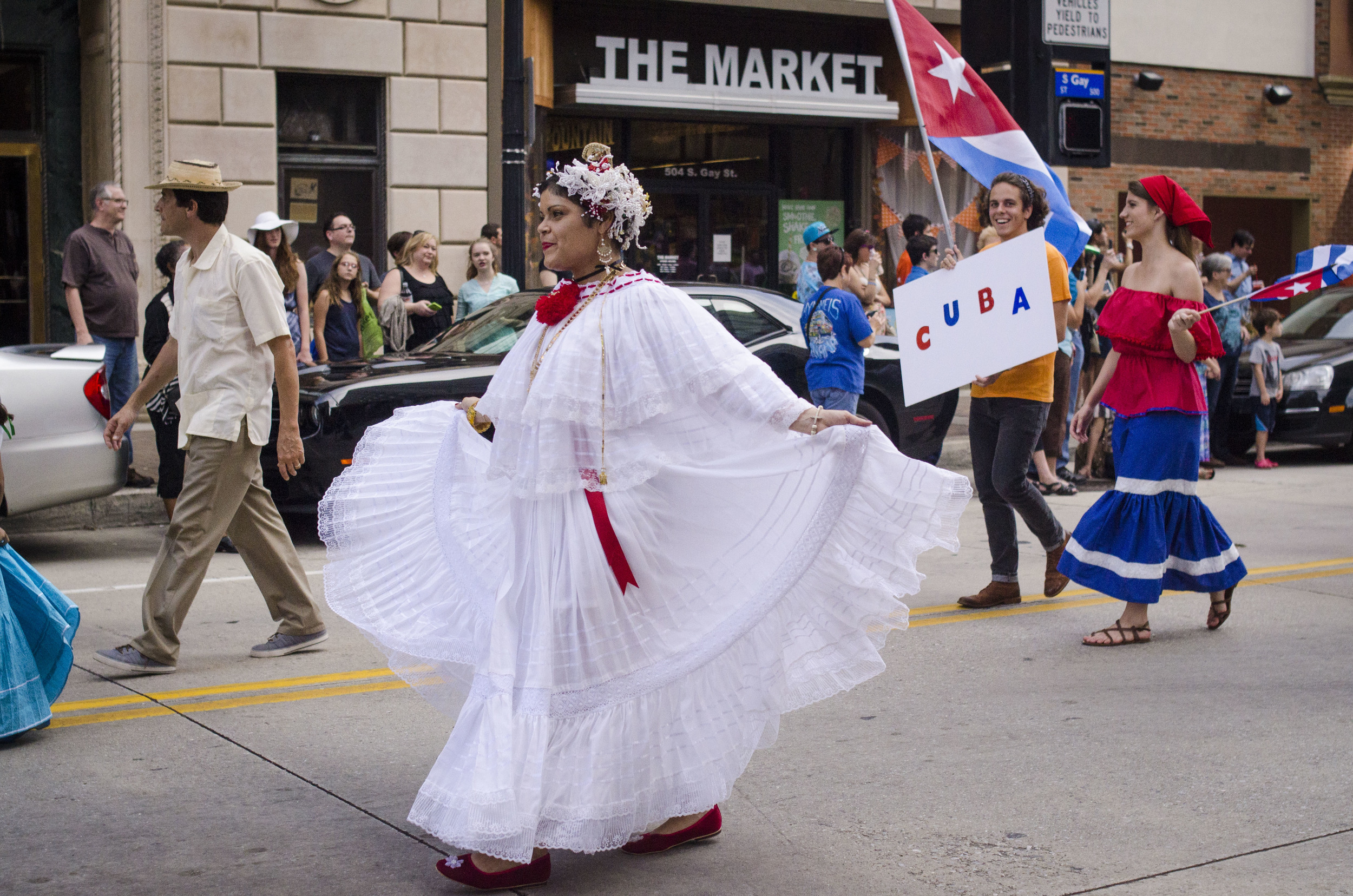 Bogotá native, Maria Rivera, strides down Gay Street while she fans out her traditional Colombian dress.