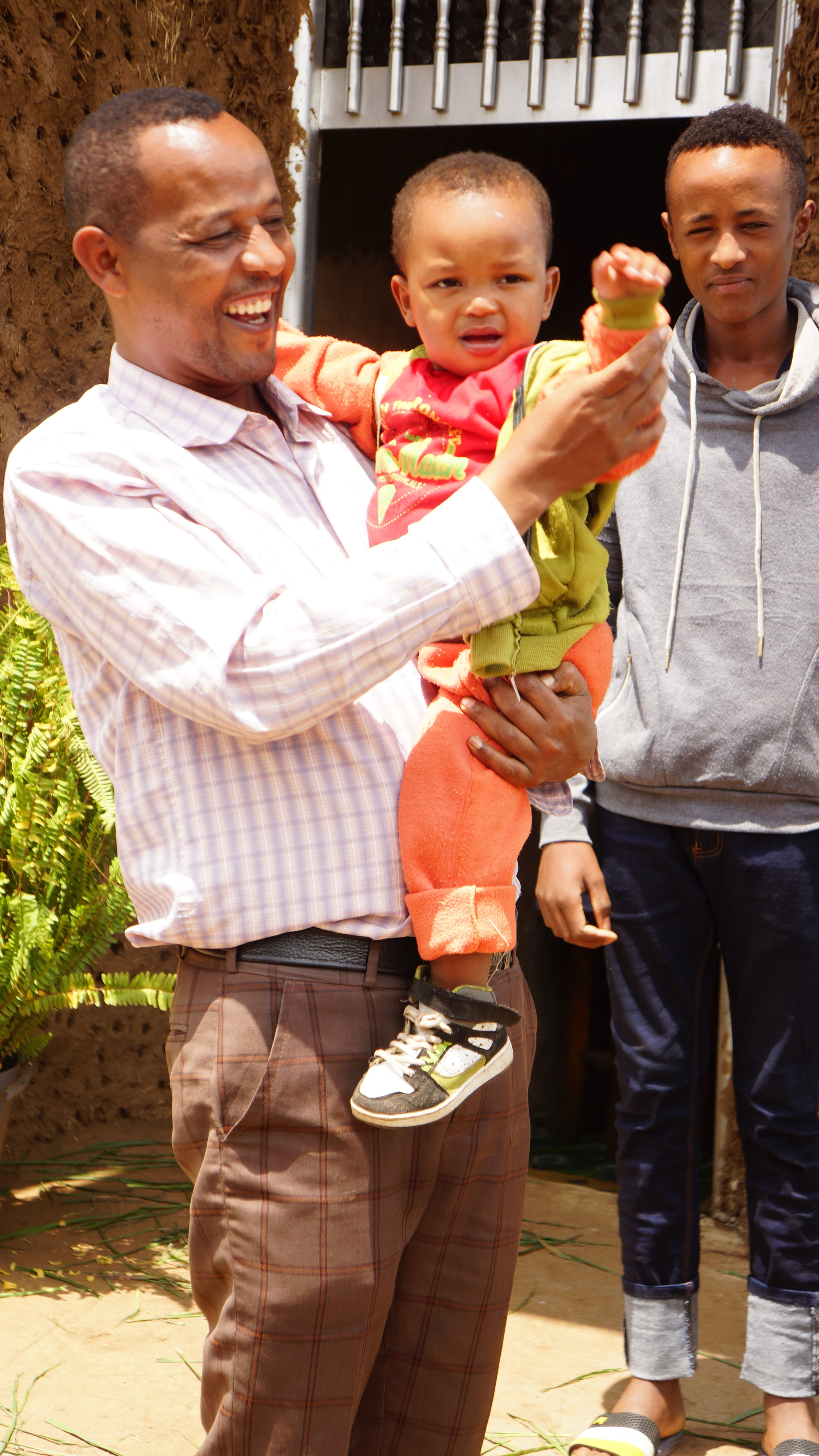 Sintayu T. with his new father and his older brother. He has bonded so strongly with his new family, and is clearly loved and cherished as he deserves to be.