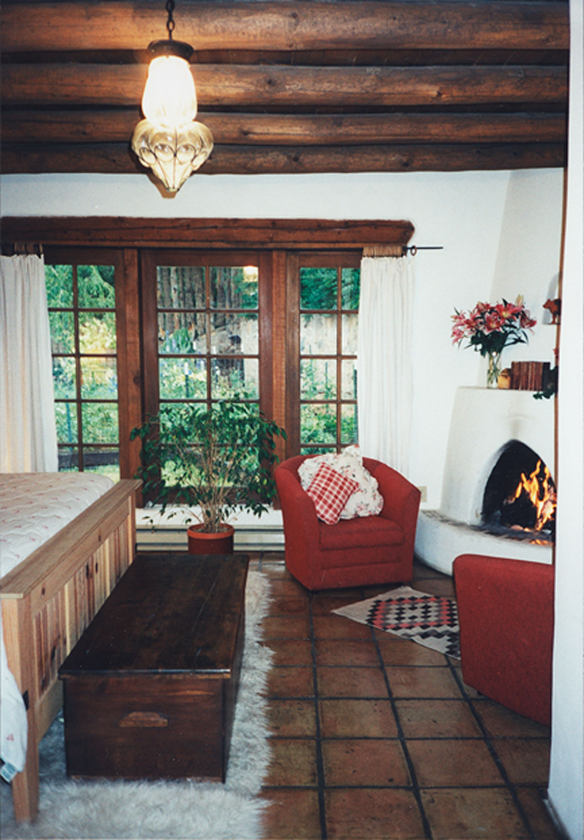B&B suite bedroom with fireplace and view to garden