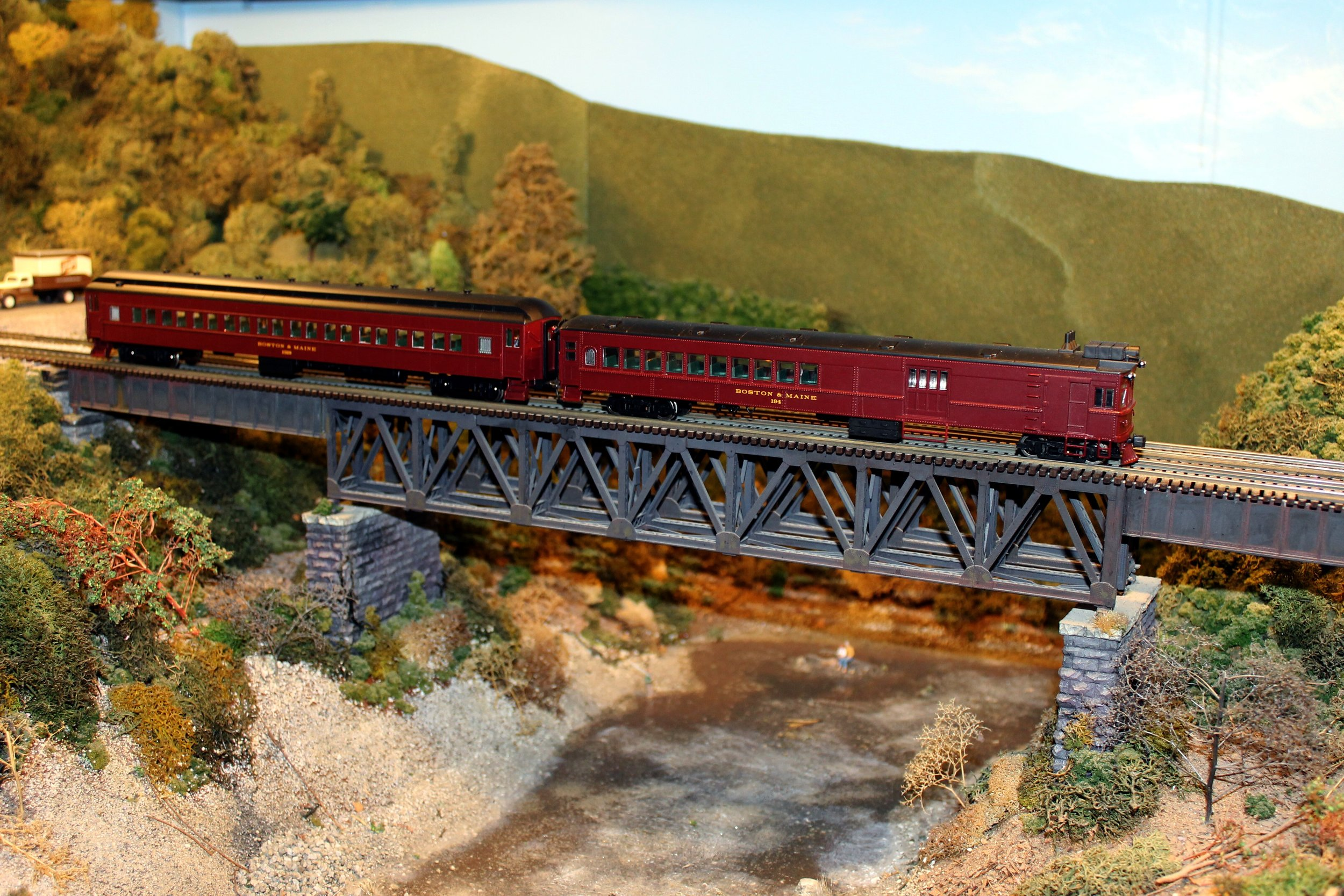 Boston and Maine doodlebug and trailer cross a typical Fitchburg Division deck truss bridge on the Nashua Valley Railroad Association layout in Shirley, Mass. Sept. 17, 2016. Mal Sockol photo.