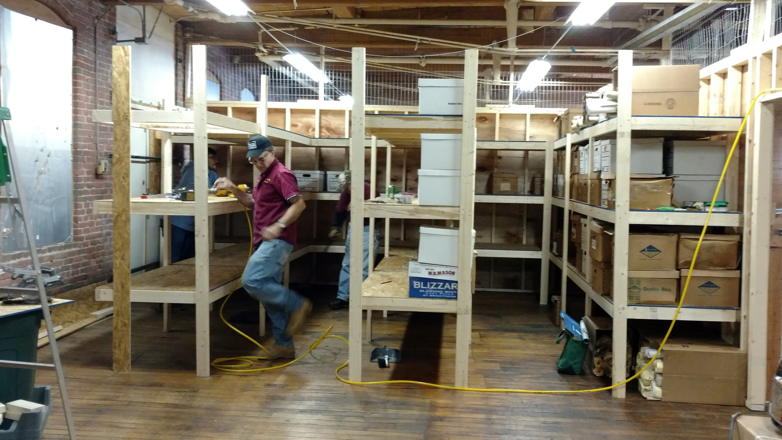 March 20, 2018. Jim Nigzus builds additional shelving. Many boxes have already been moved into the new space by Jimmy Nigzus, Rick Kfoury, Richard Nichols, and Tim Hairston. Staff photo