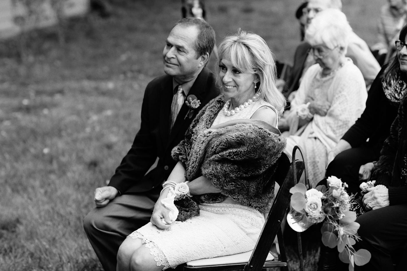 Grooms parents watching wedding ceremony