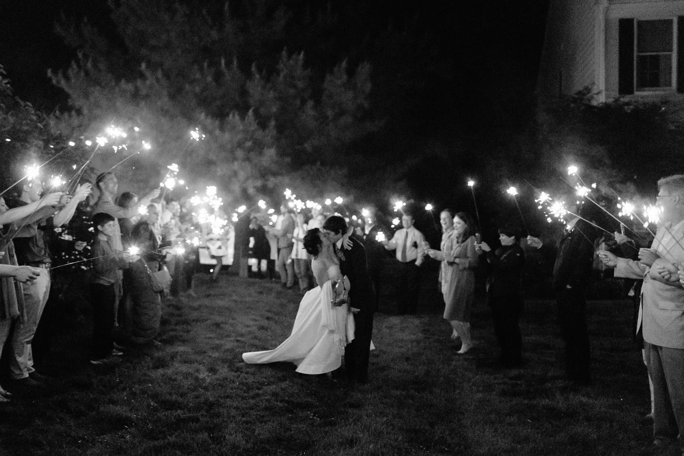Bride and groom kissing sparkler sendoff