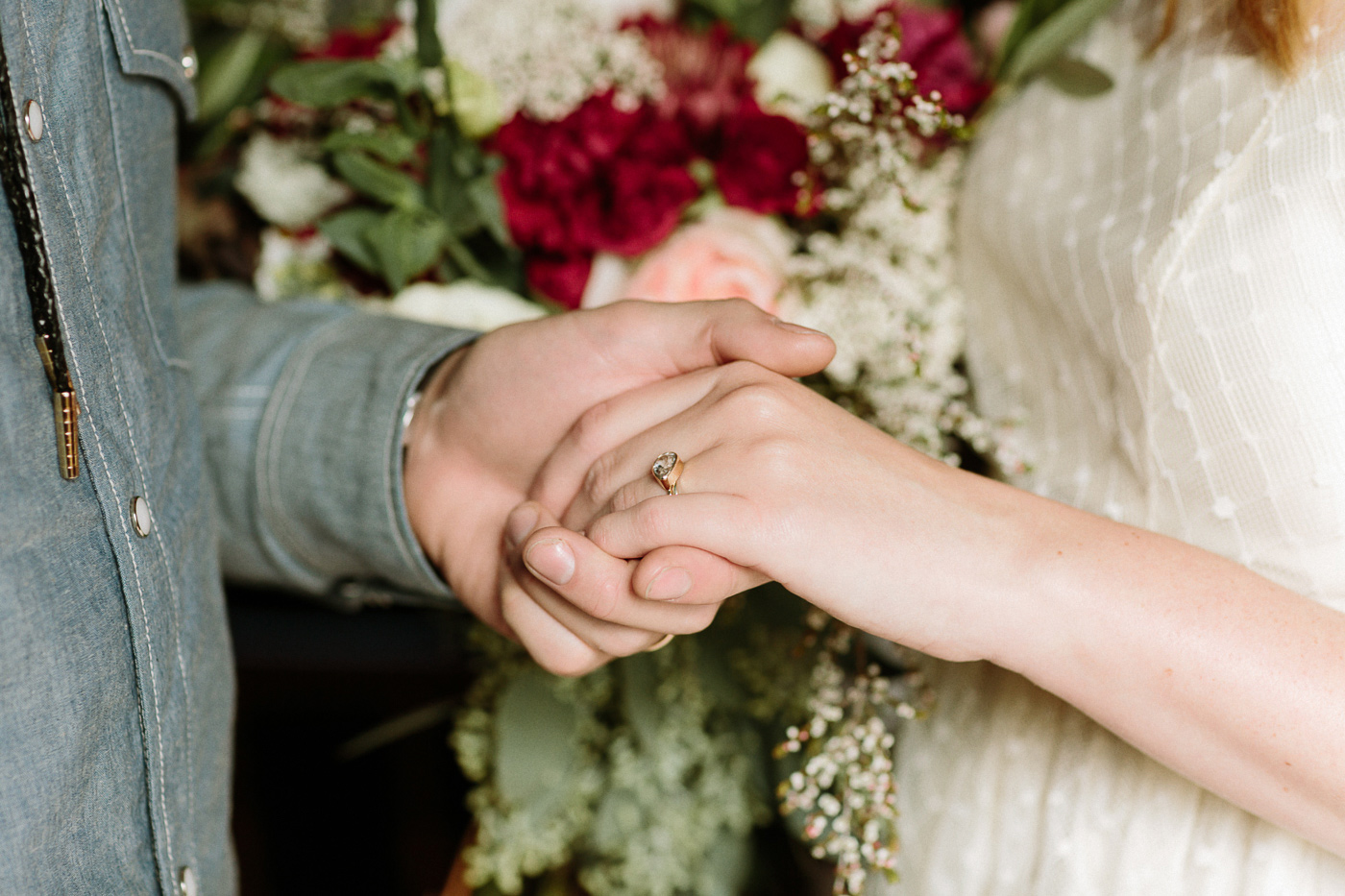 Bride and groom holding hands ring flowers