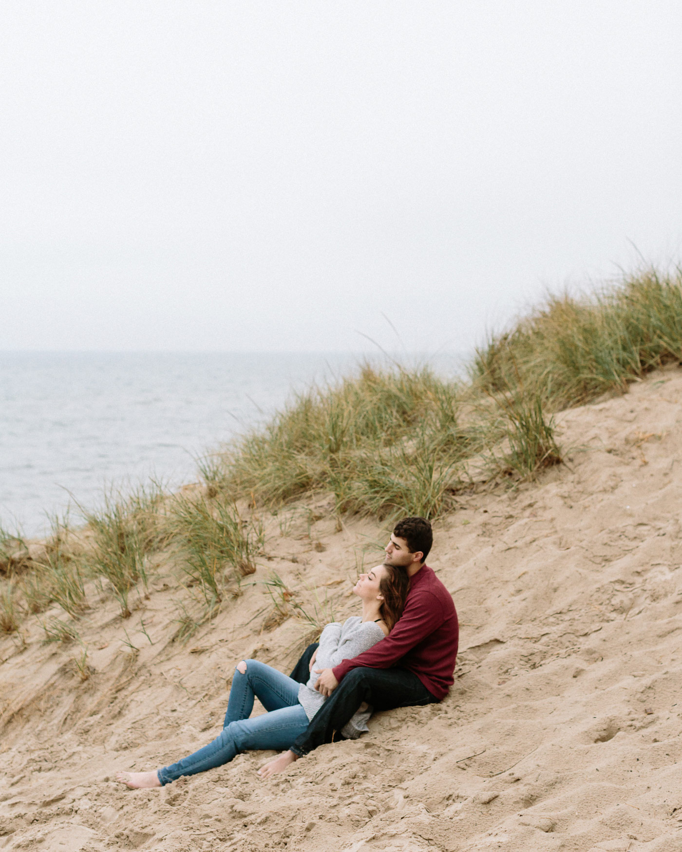 Couple sitting in sand beside Lake Michigan