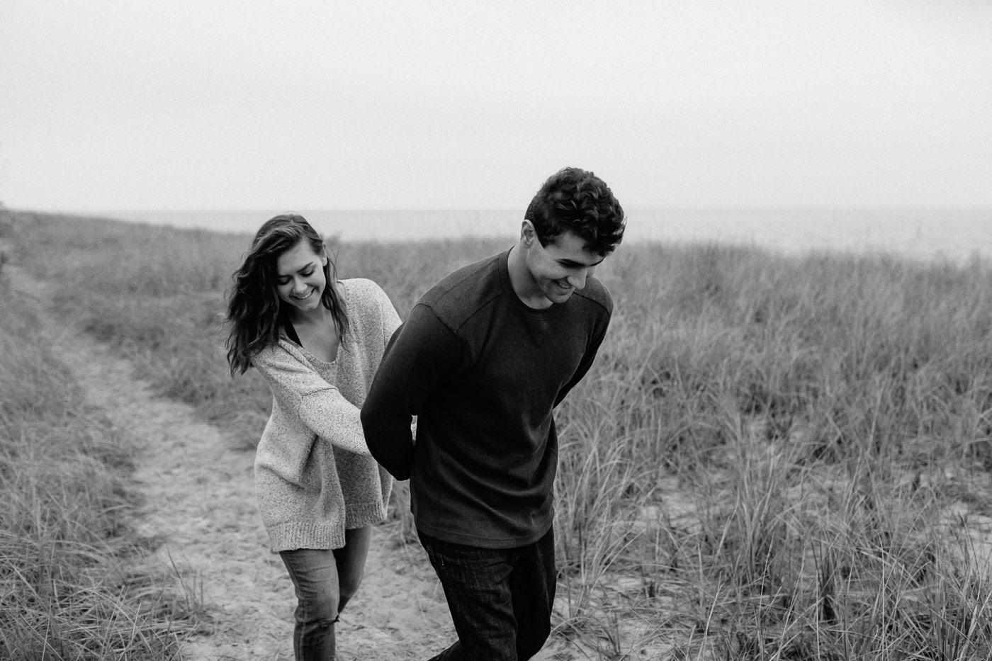Couple walking and laughing along beach path
