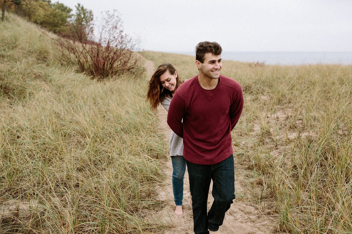 Couple walking and laughing at Saugatuck Dunes State Park