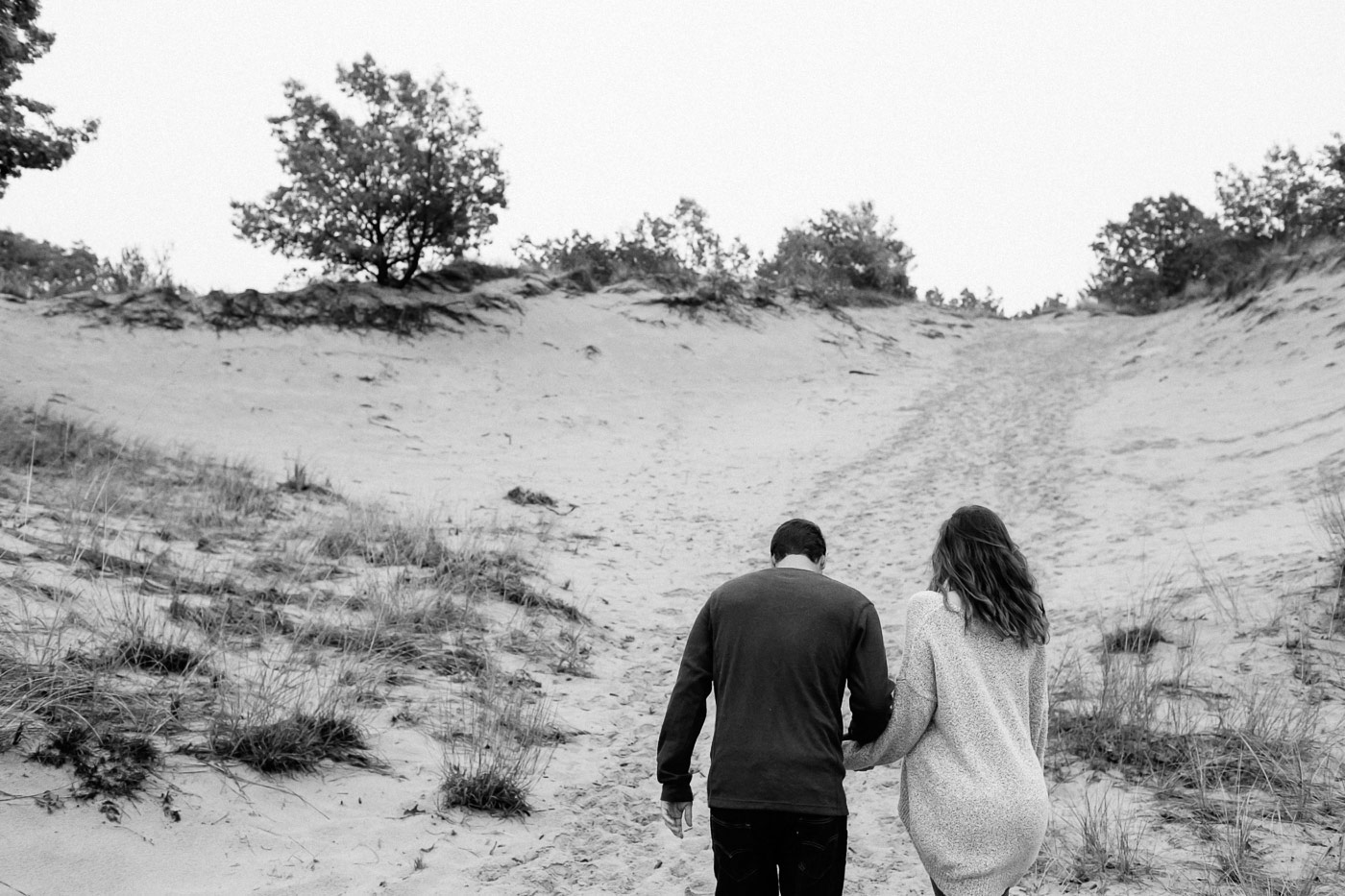 Couple walking up dunes