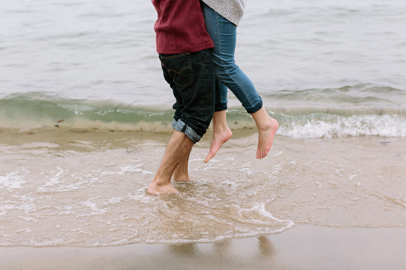Close up of feet couple hugging in the surf