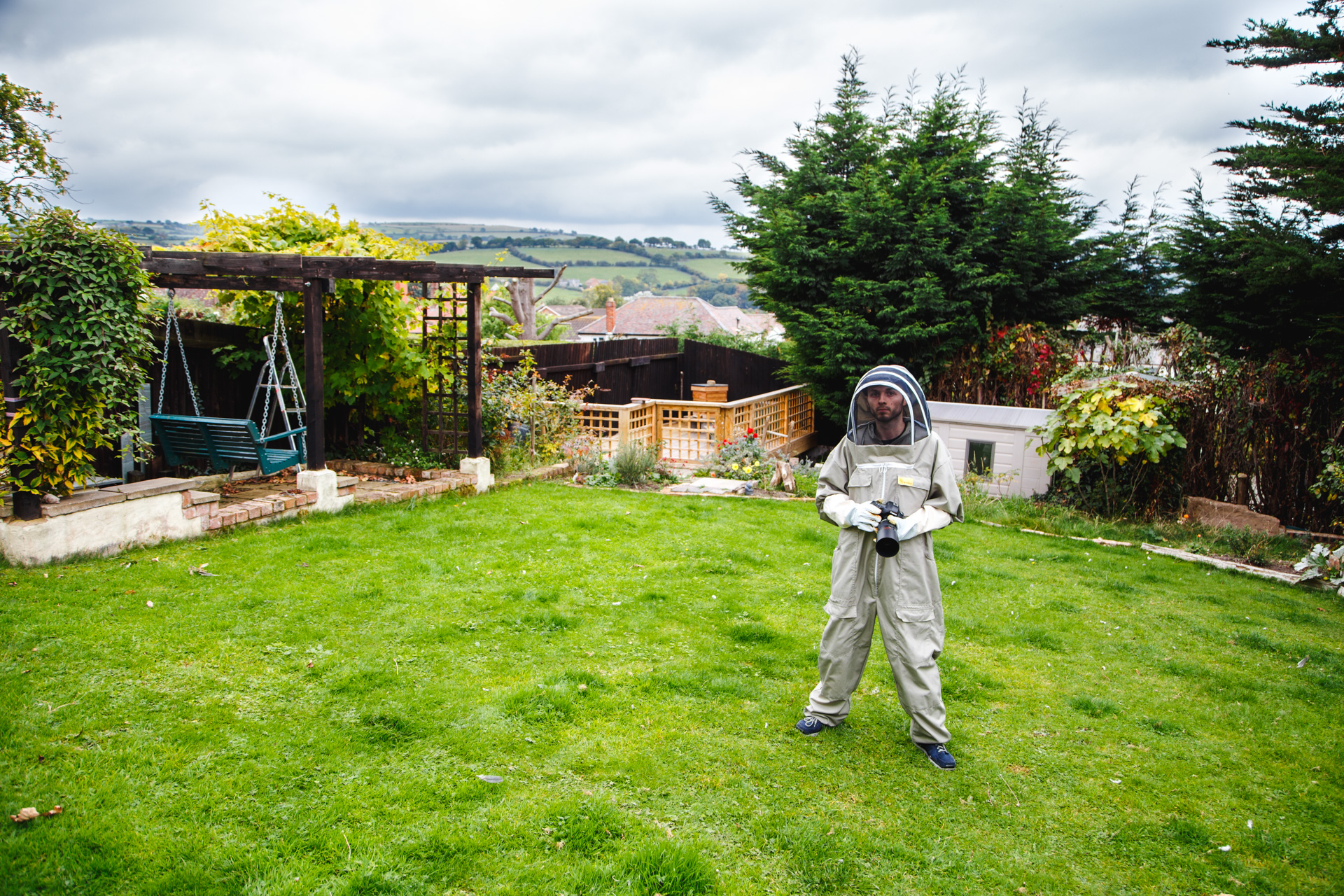Me, in the suit, in my parents garden. The hive is in the centre of the background.