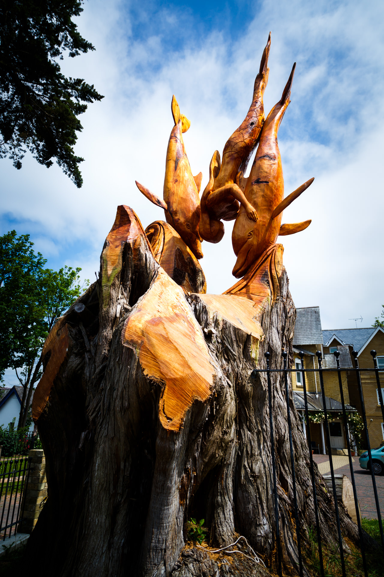 Mermaid and dolphins carved out of a tree.