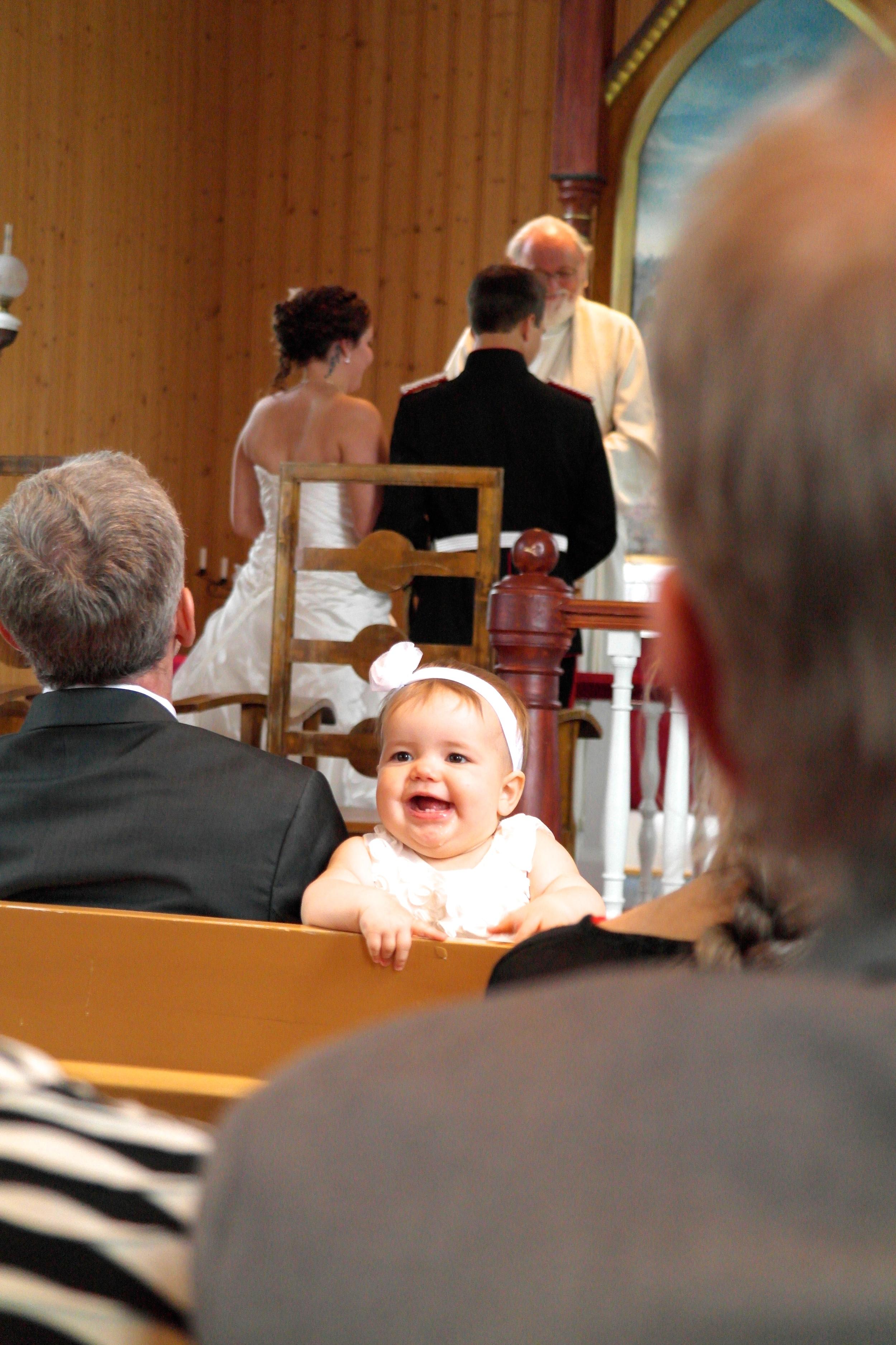 """Aria, jenta til Barbro og Øystein sjarmerer """"publikum"""" i kirken."""