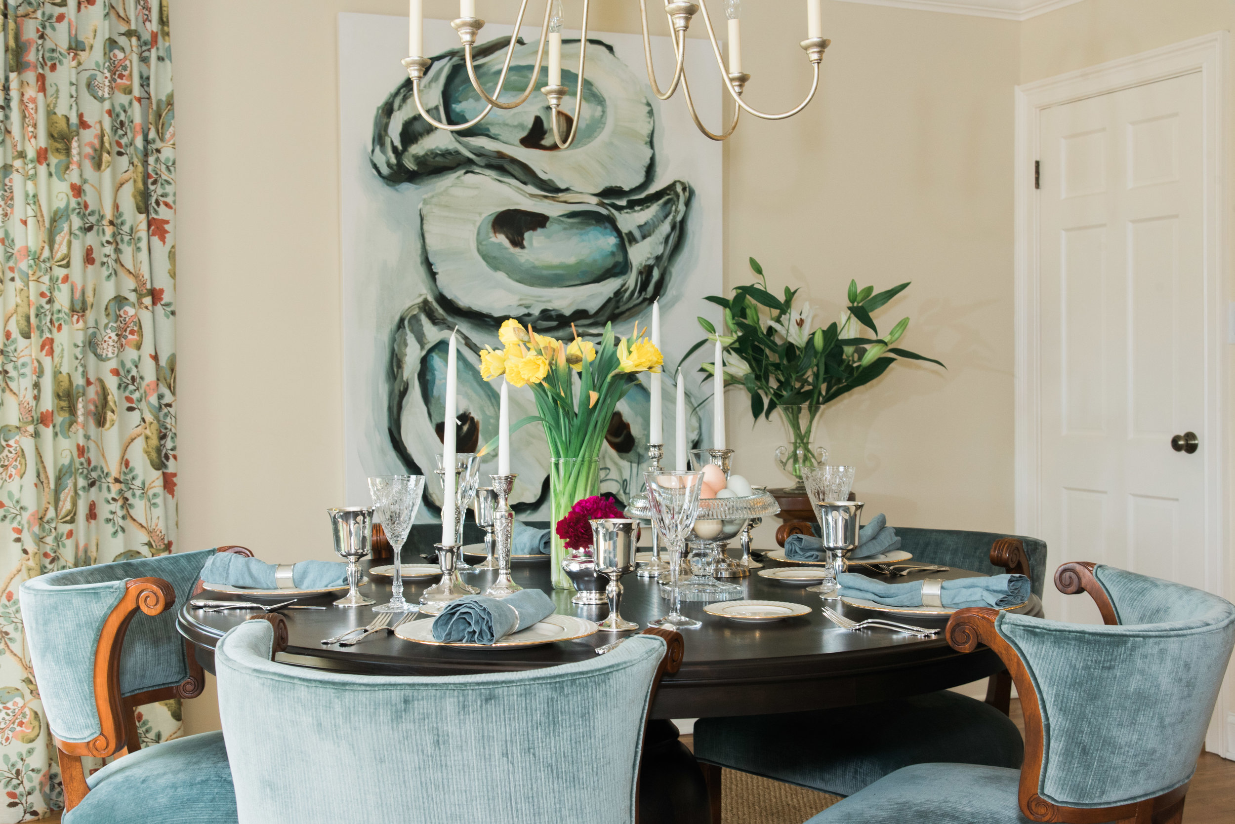 Like the house, this table is luxurious without being overdressed.     Artwork:  Bellamy   |   Chairs:  H  ickory Chair   | Chair Fabric:  Pollack   |   Table: Custom design by Calvert Dean Design|    Chandelier:  Currey & Company