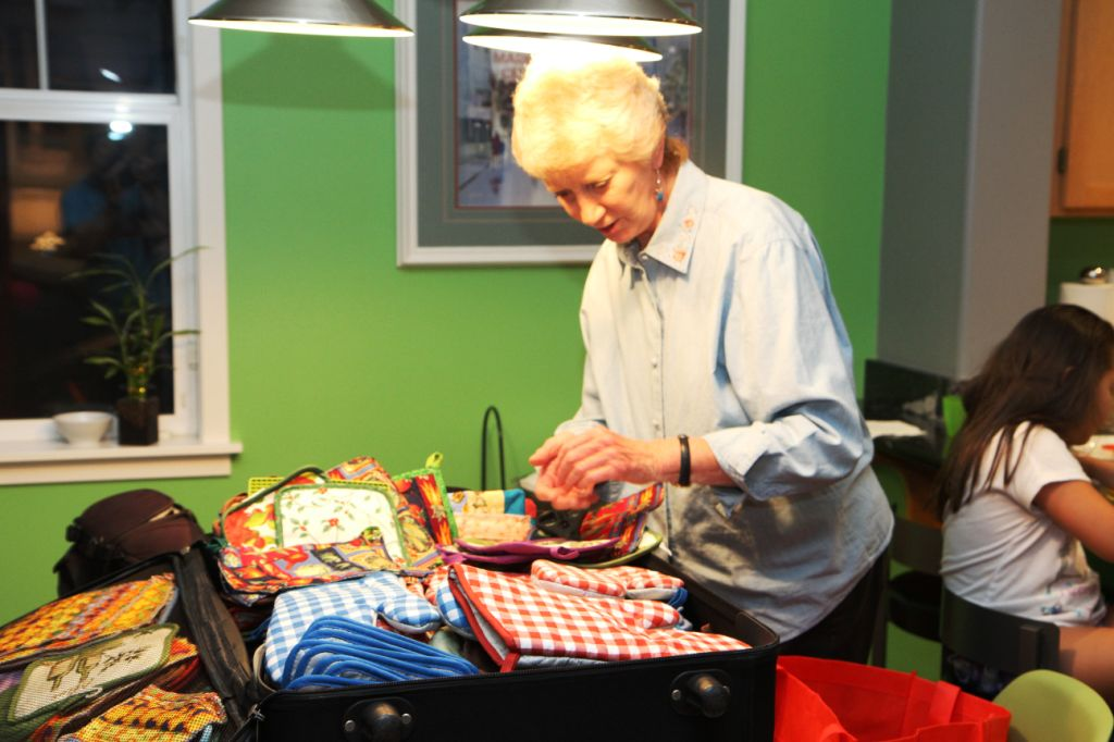 Team member Diane Malone packs pot holders to be given as gifts to those who receive a stove.
