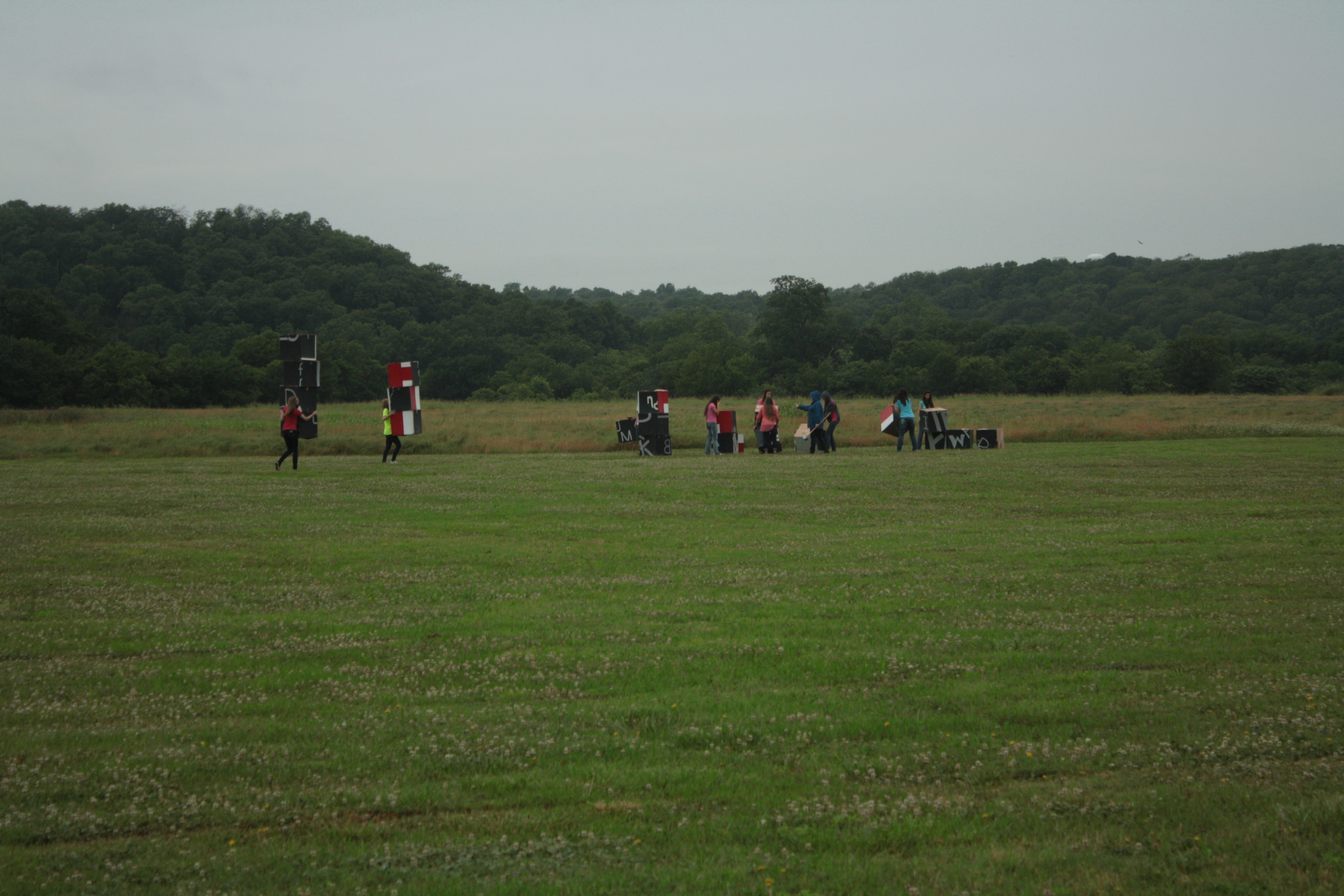 The students carrying their boxes to the middle of the field.