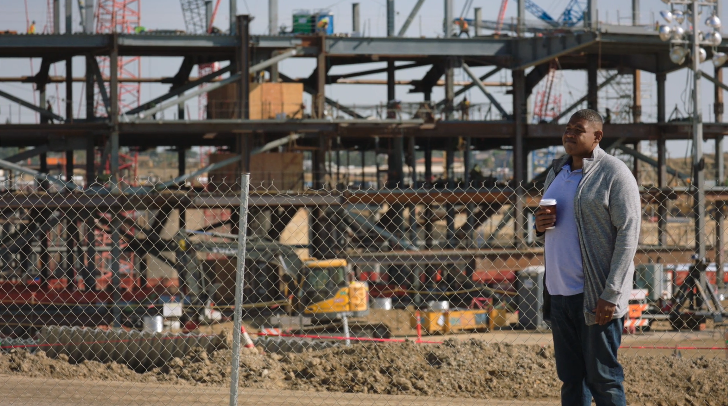An underdressed Charles Greane loiters around a construction site.