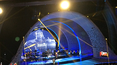 """Pointing to herself as a """"Survivor"""", Adrienne Slaughter appears on video screen behind LIVE performance by Jennifer Hudson, Common and Lupe Fiasco at Stand Up To Cancer Telethon at the Dolby Theater on September 5, 2014."""