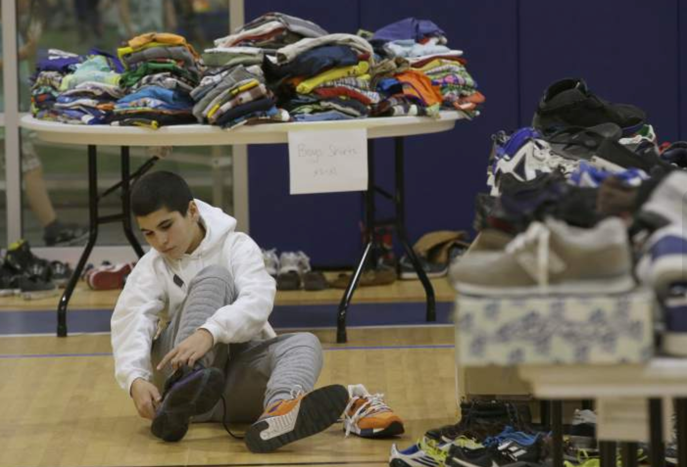 "From  Press Democrat : ""Mehdi Latrache tries on shoes at a donation center for victims of the recent wildfires..."" (Photo Credit: AP Photo/Rich Pedroncelli)"
