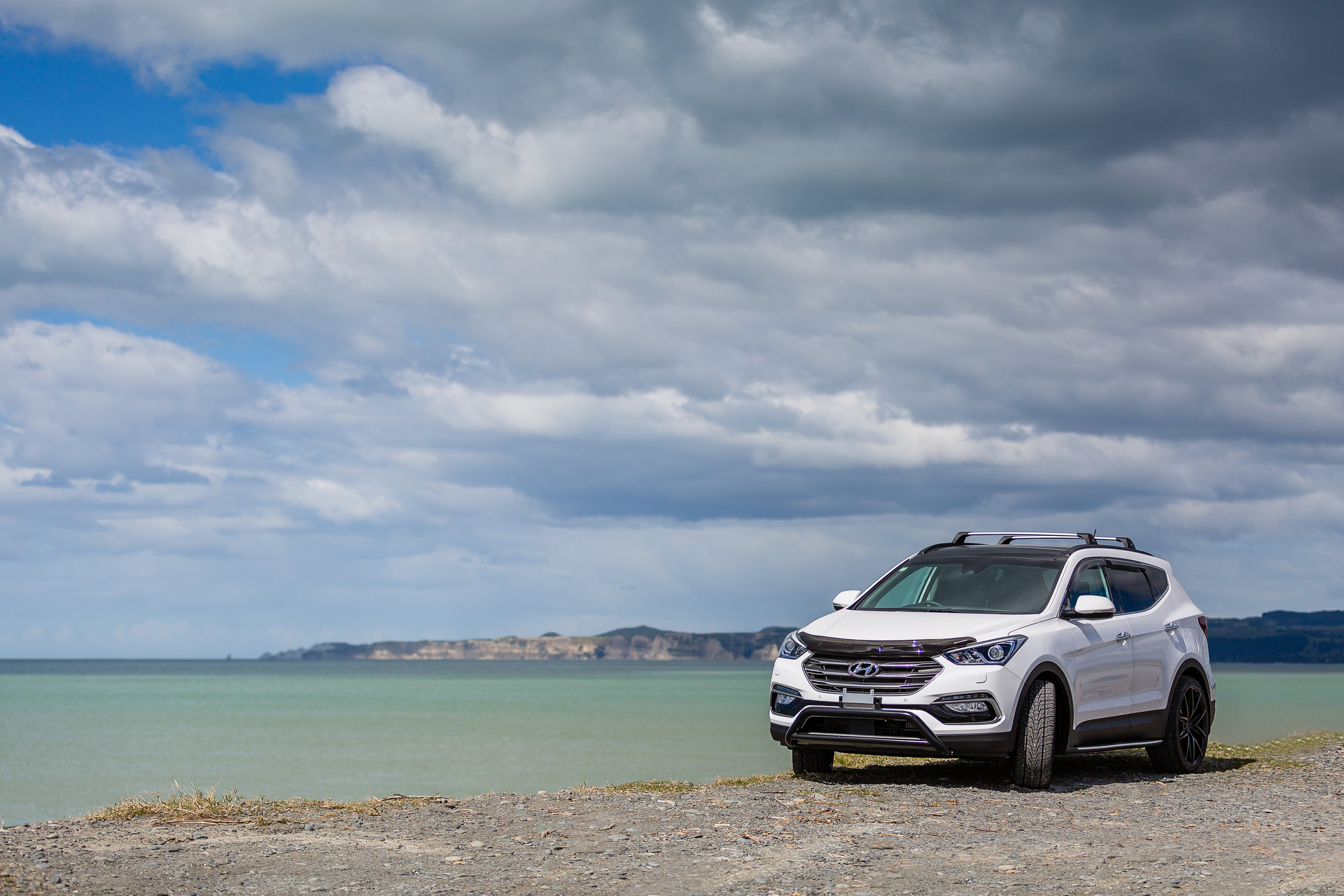 Hyundai SantaFe at the beach with Hawke Bay and Cape Kidnappers as a backdrop