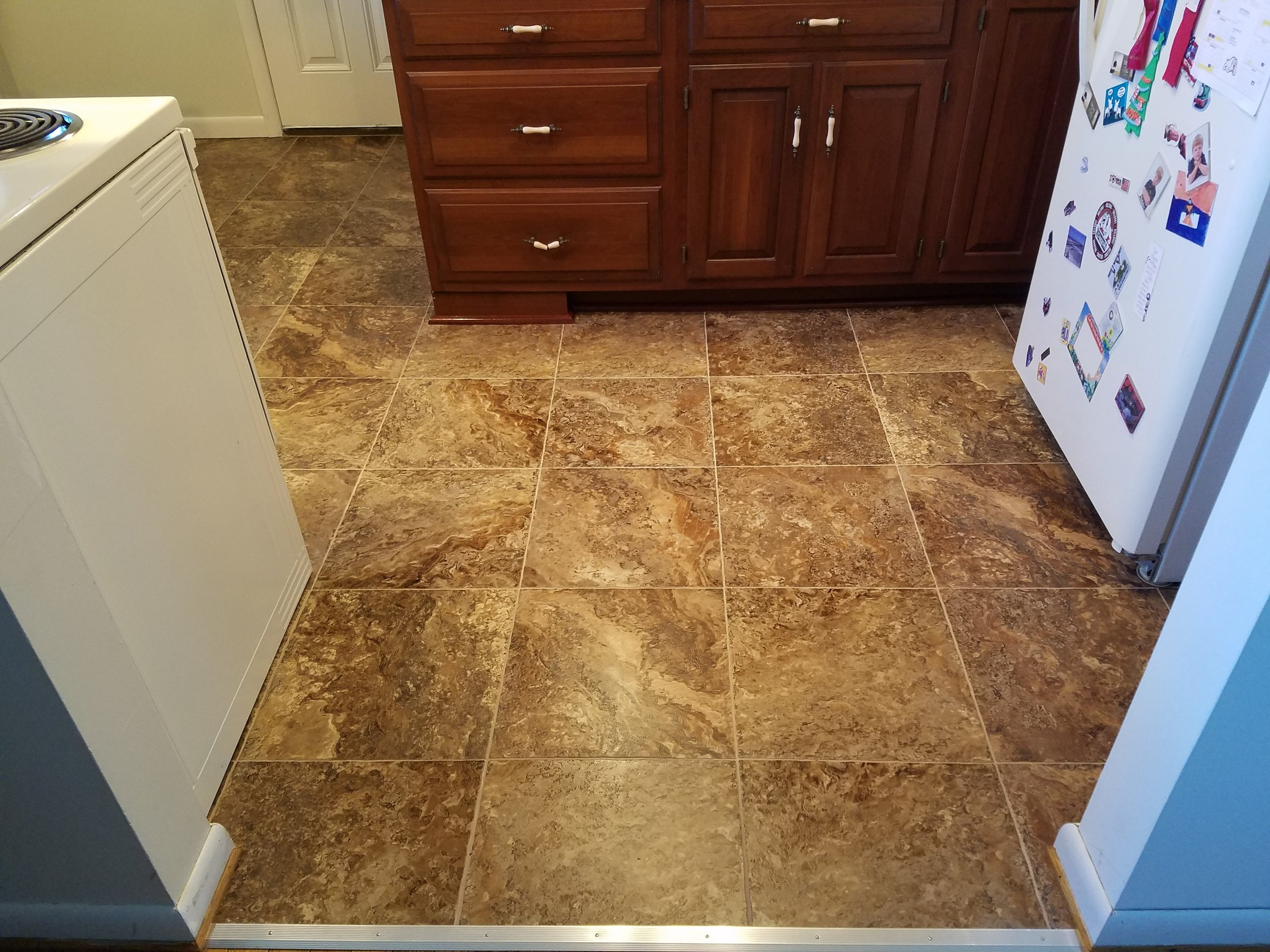 Armstrong luxury vinyl tile with grout installed in a kitchen. Vinyl tile gives the look of ceramic or porcelain tile but with a softer and warmer feel. Products such as this are also more budget friendly then standard tile.
