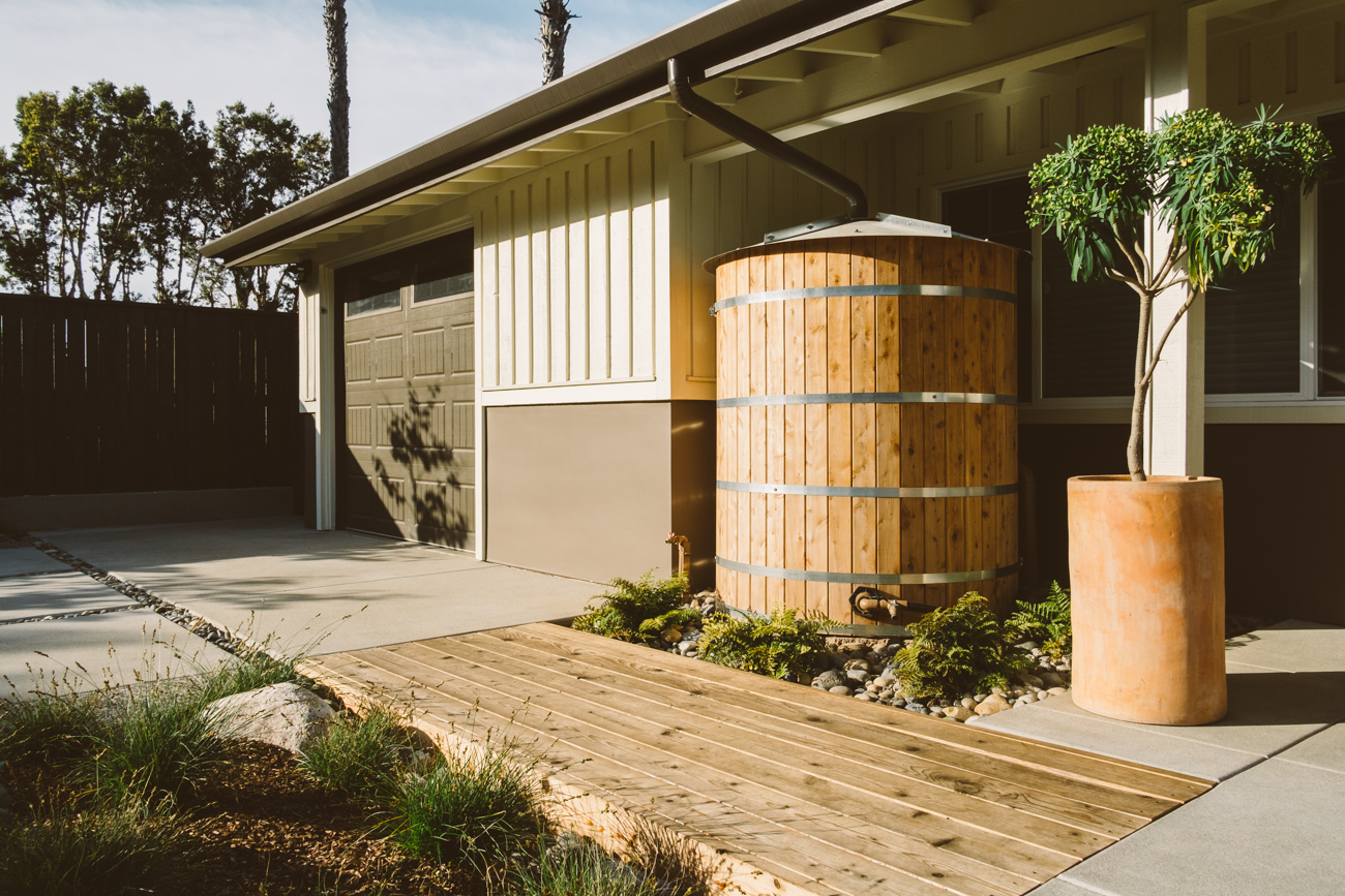 Rainwater harvesting is an easy way to collect water and use it again for your landscape or dishwashing. Not all containers have to be an eye sore either, this one pictured above gives this house a rustic and down-home feel.
