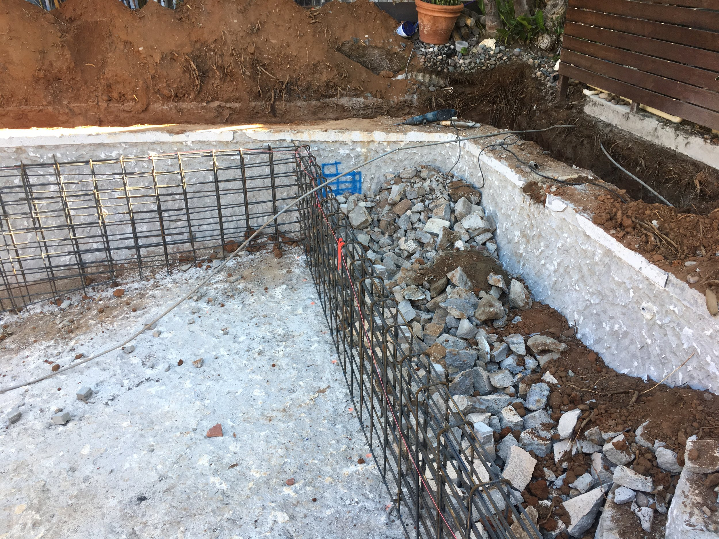 This is a picture standing on the other side of the pool looking towards the back fence. The rebar framing will get filled with concrete, creating the new edge of the pool, and the area in between these new walls and the existing walls will get filled with dirt and rock.
