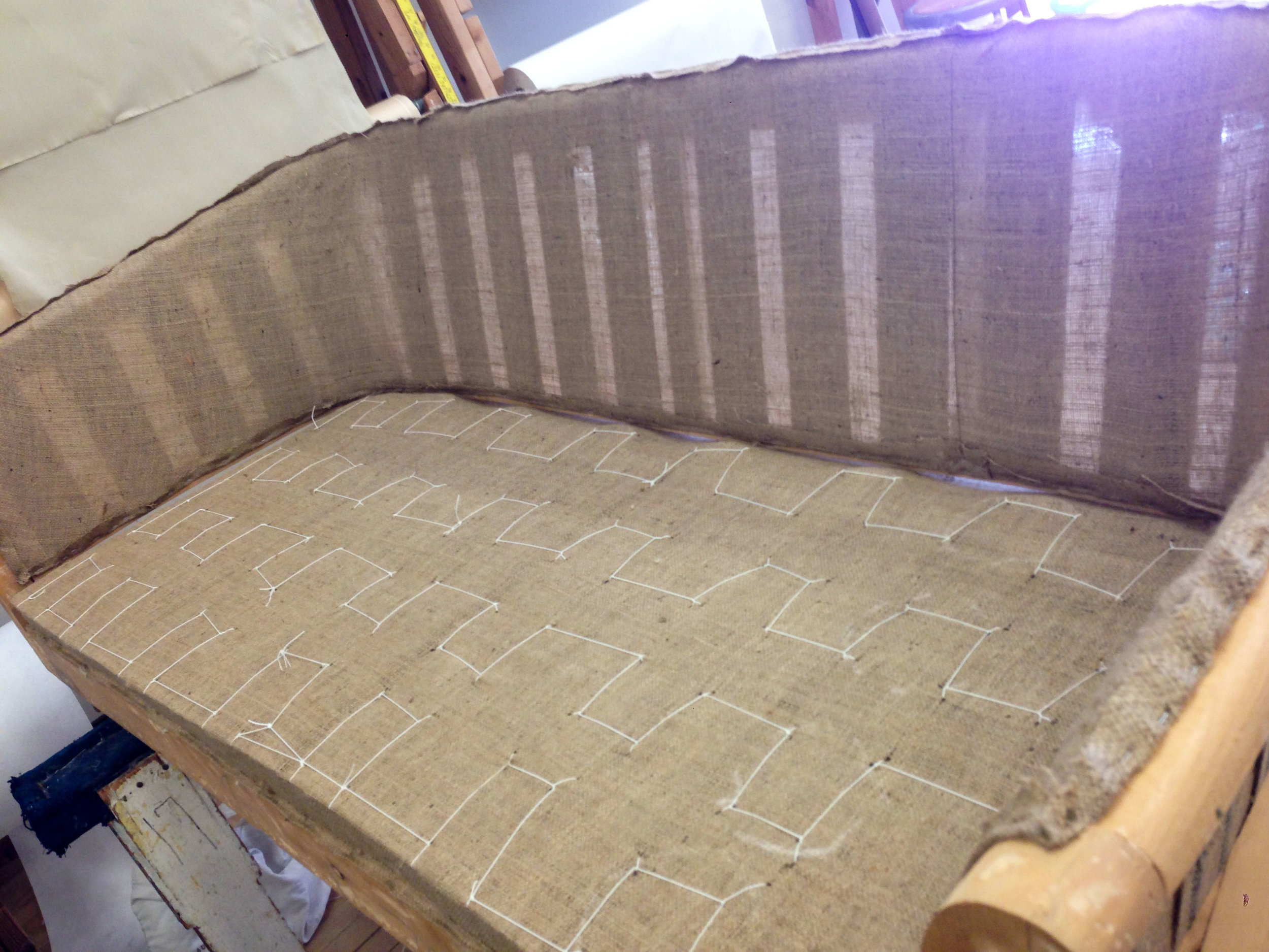 Burlap, like all other steps in the upholstery process, is stapled and hand sewn to the frame. THIS picture is burlap sewn to Coil Springs.