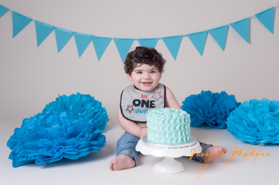 Baby one year old boy smiling behind blue cake for his Cake Smash Session in Staten Island, NY