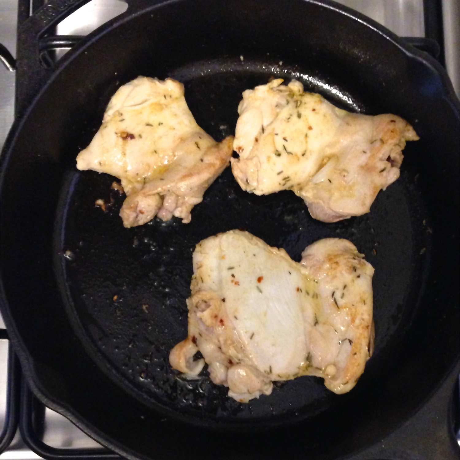 Lightly cooked chicken on skillet.