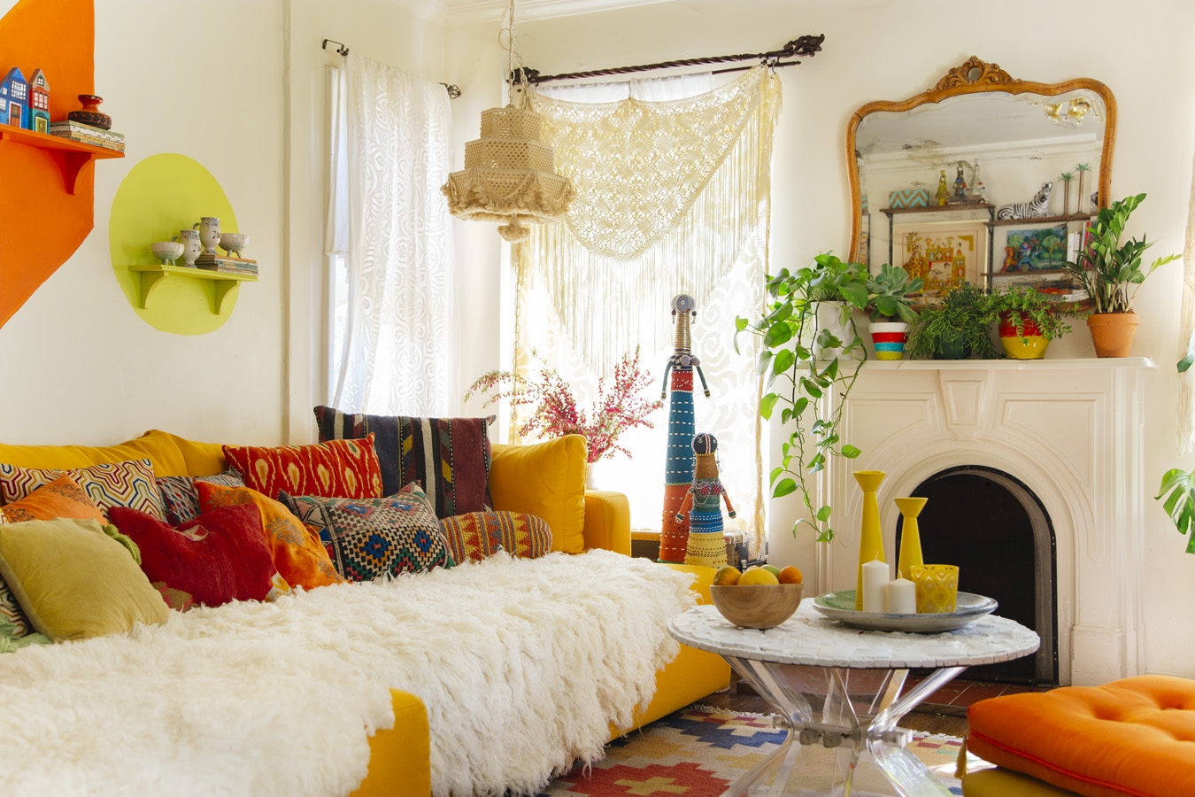 Photo from the book The New Bohemians: Cool and Collected Homes.  A Living room with white walls, a bright yellow couch, white fur throw, and lots of yellow, orange, and lime green accessories