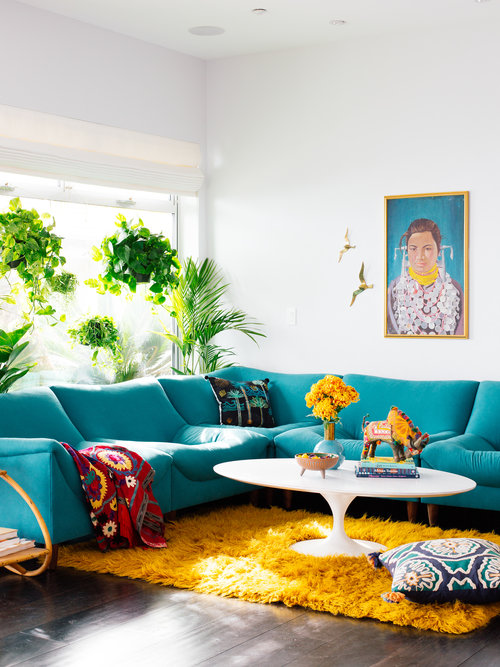 Justina Blakeney design - living room with teal couch, yellow shag rug, and a white tulip coffee table