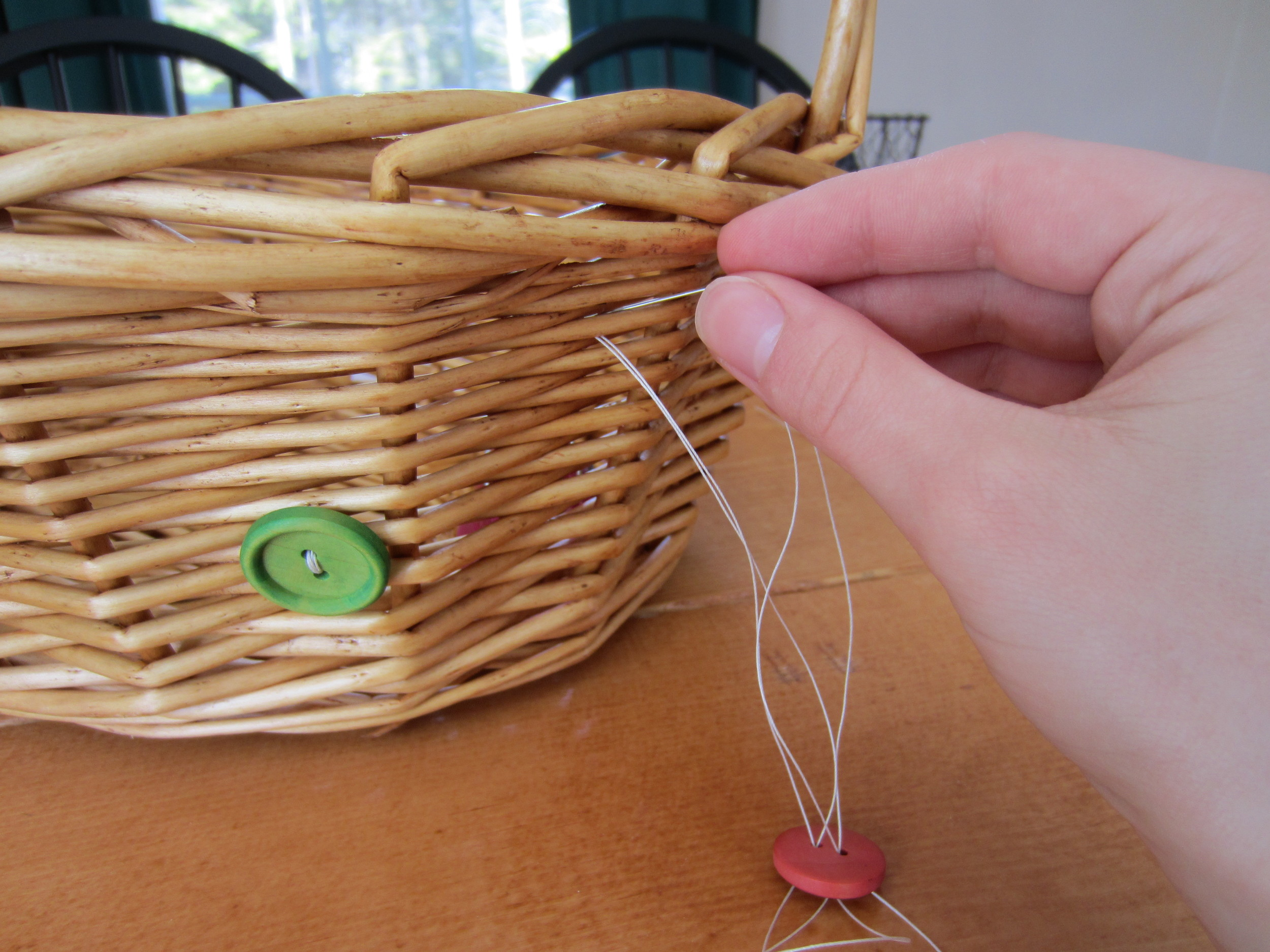 """""""Sewing"""" the buttons to the basket."""