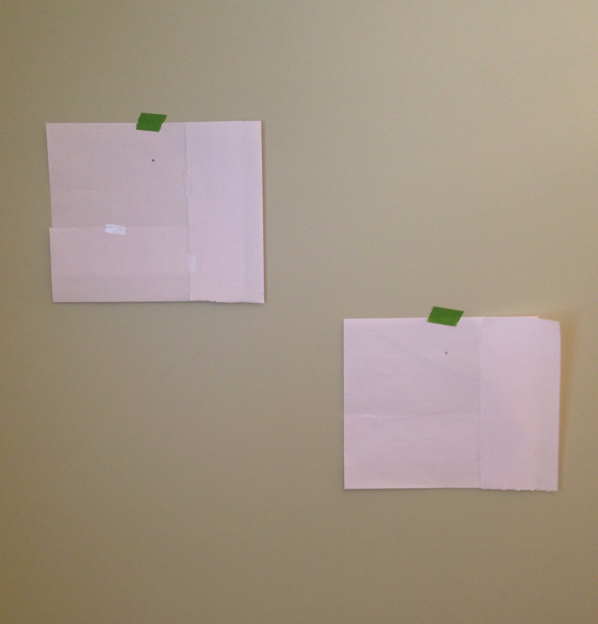 Putting up paper templates to hang gallery wall