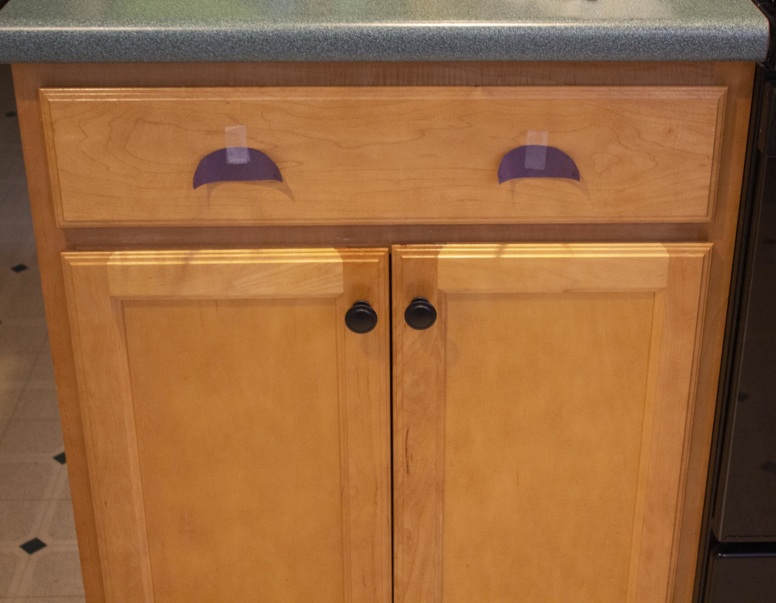 Deciding on drawer pull placement. (Note that while the lower cabinet knobs are each in the correct place, they look off since the cabinet doors are uneven - this can be fixed by adjusting the cabinet door hinges, which I did once I was finished installing all the hardware.)