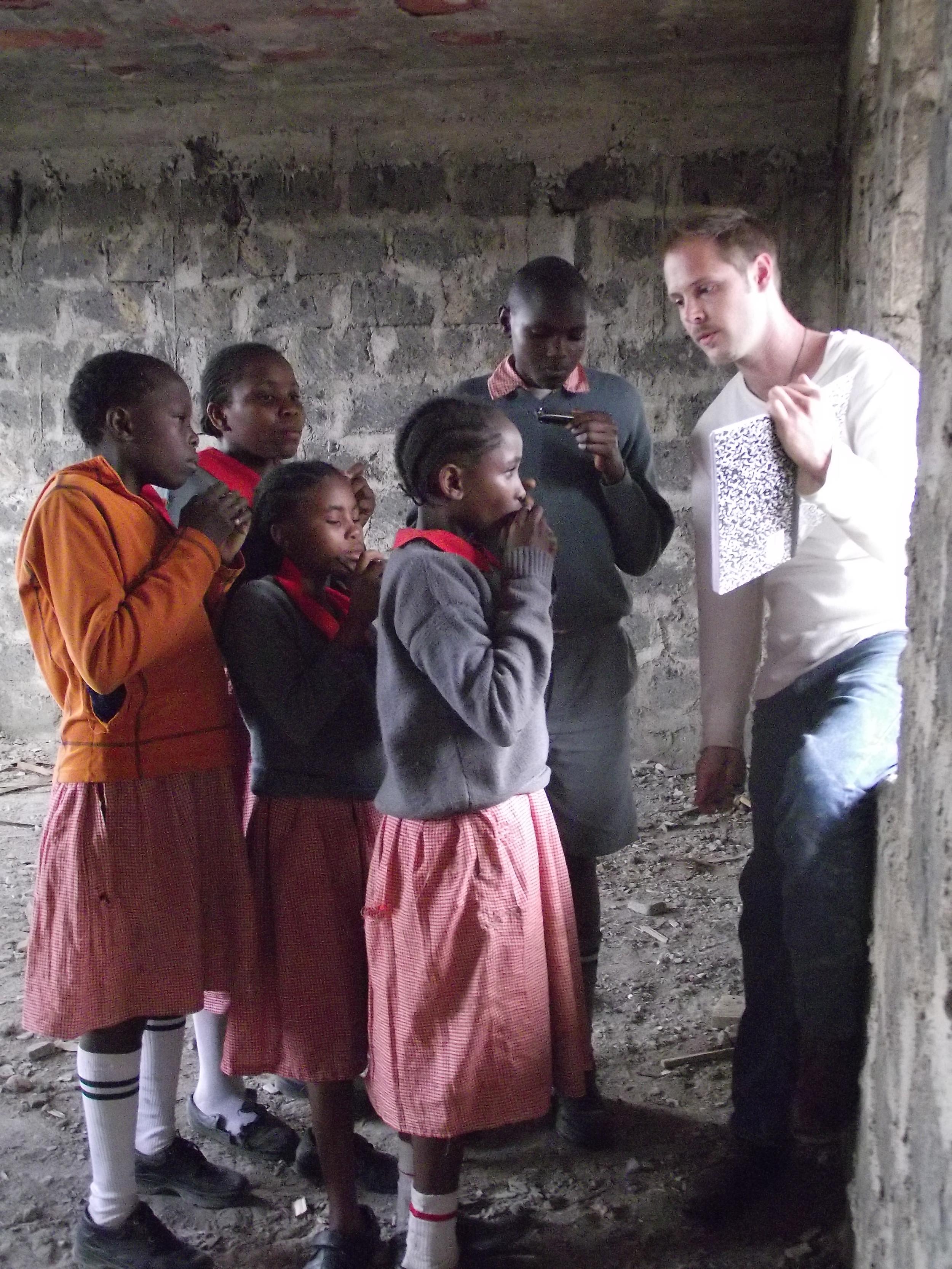 Music - Billy teaching harmonica Mathare.JPG