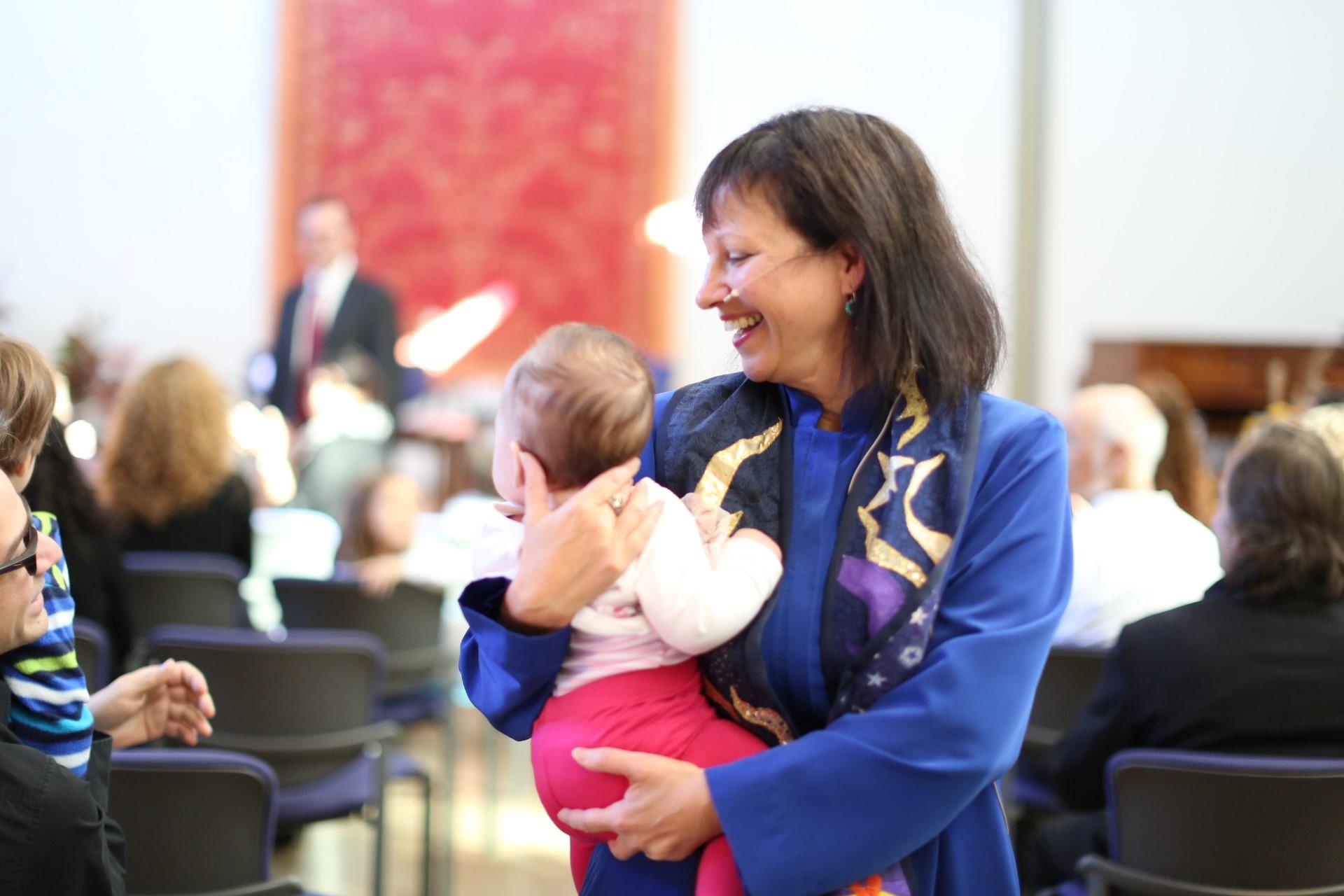 Rev. Diane Rollert performing a child dedication.