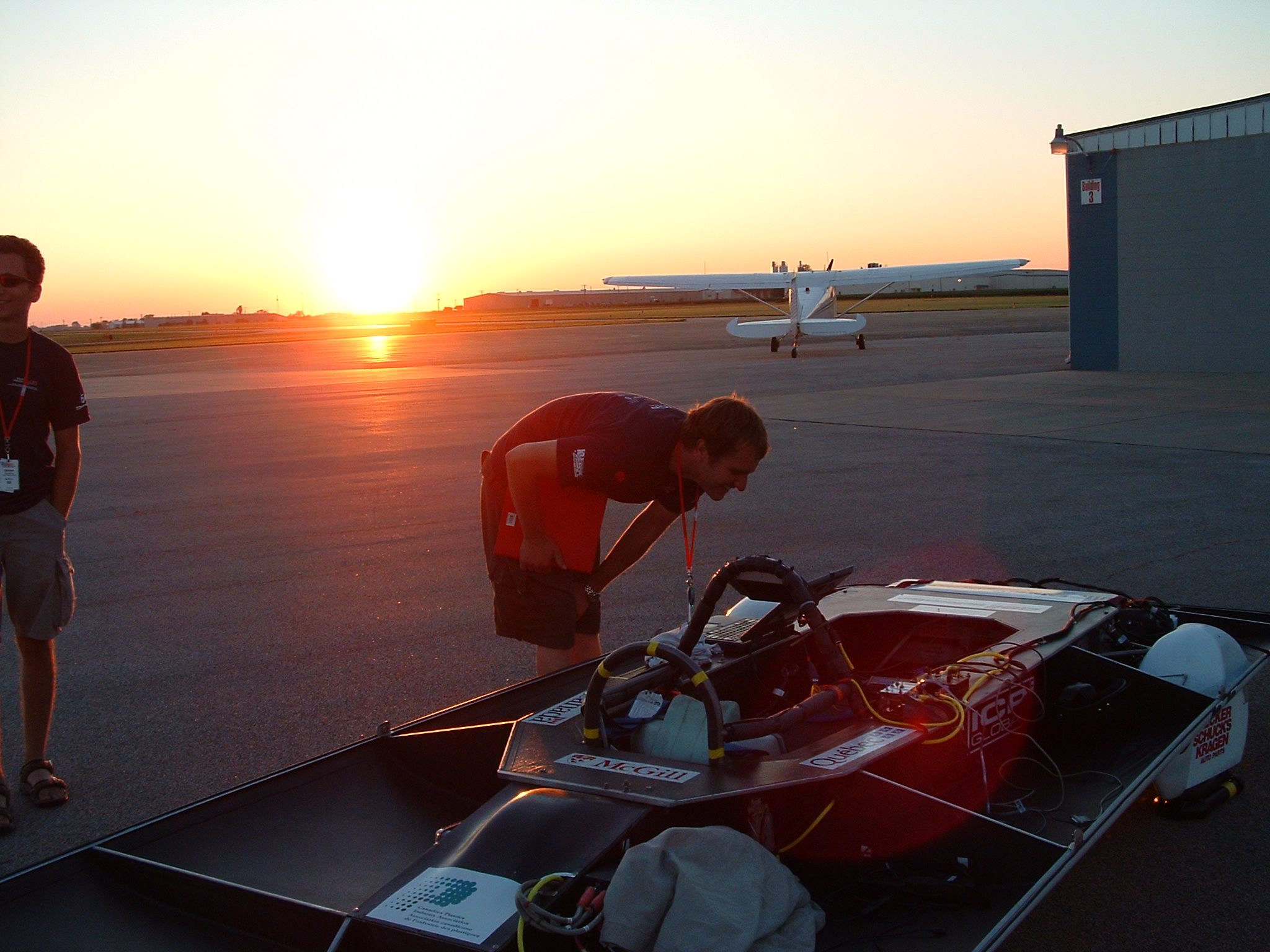 Matt Smith looking over telemetry on the car as Simon looks cool and the sun sets.
