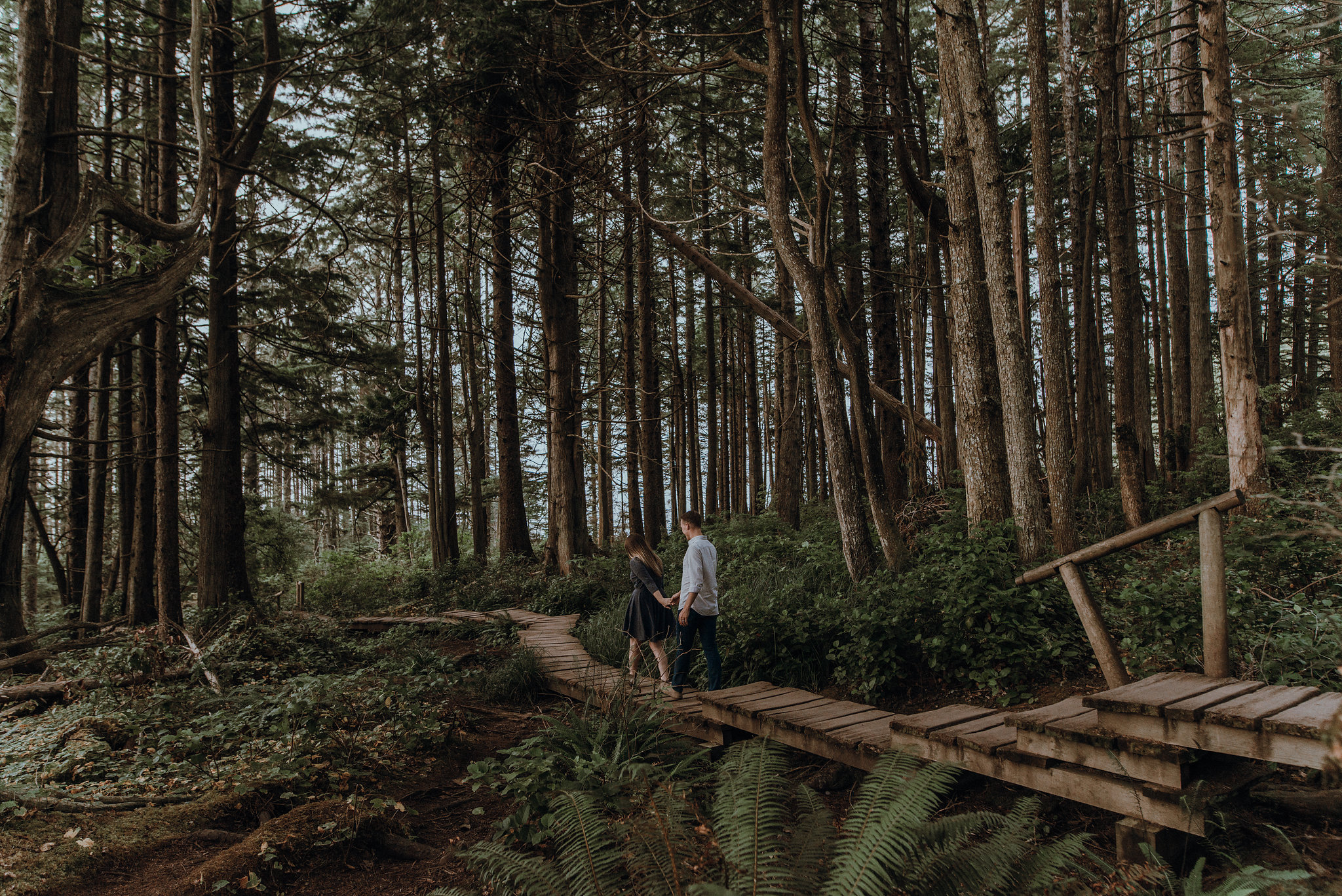 Pacific Northwest couple holding hands at engagement session and walking through forest.