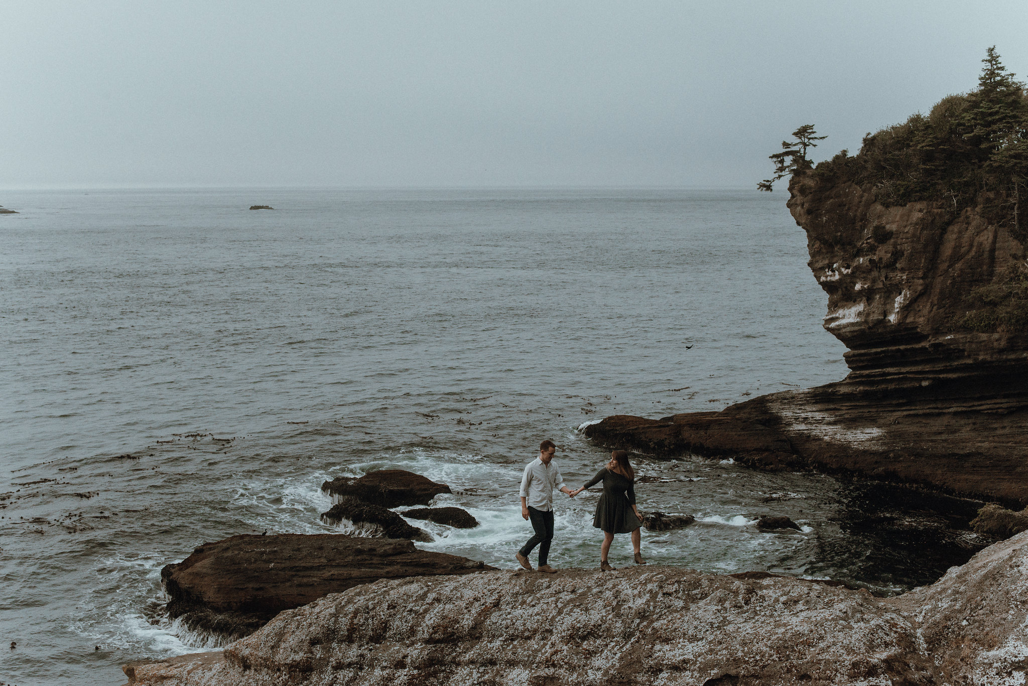 Couple holding hands and walking across rocks at ocean rocky coast.