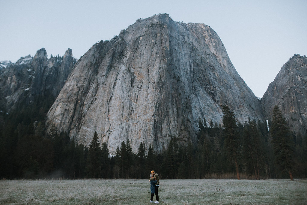 Engaged couple holding each other in Yosemite Valley in front of granite rock formation.