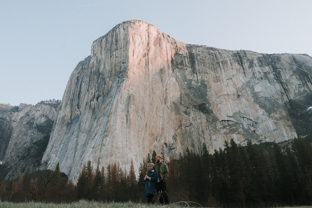 Couple relaxes in Yosemite National Park with El Capitan in the background.