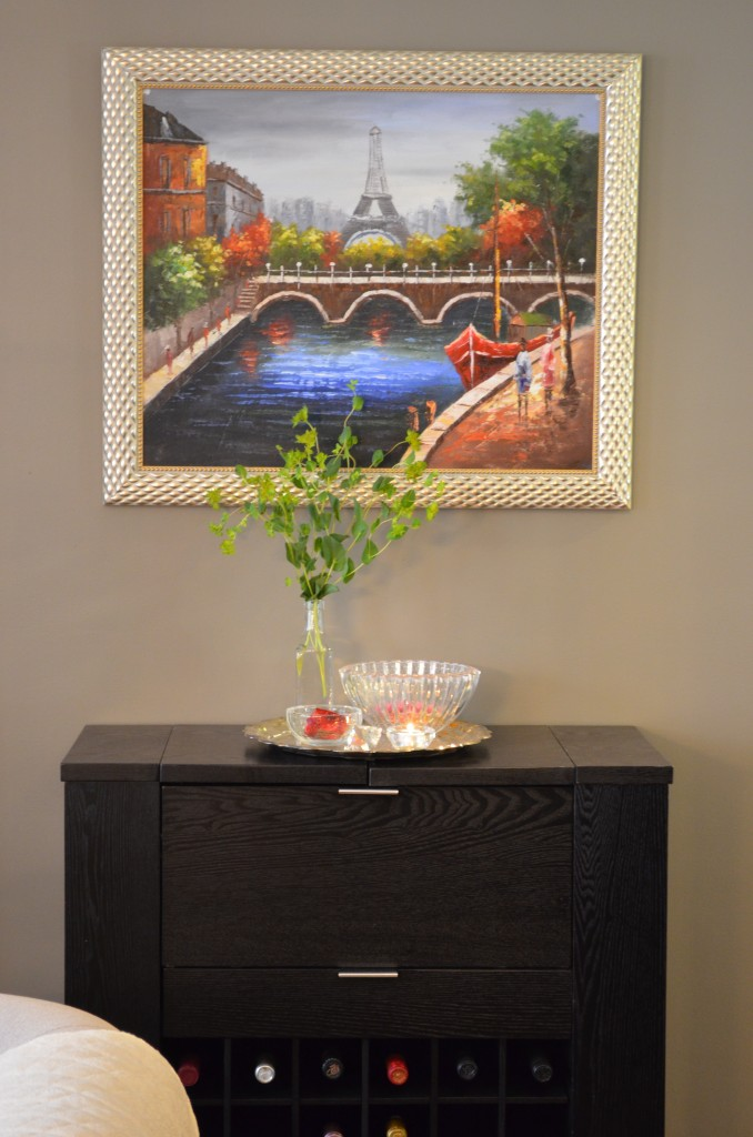 """The """"filler"""" greens from the bouquet of roses look completely chic in a simple glass bottle set atop a silver tray and other bobbles."""