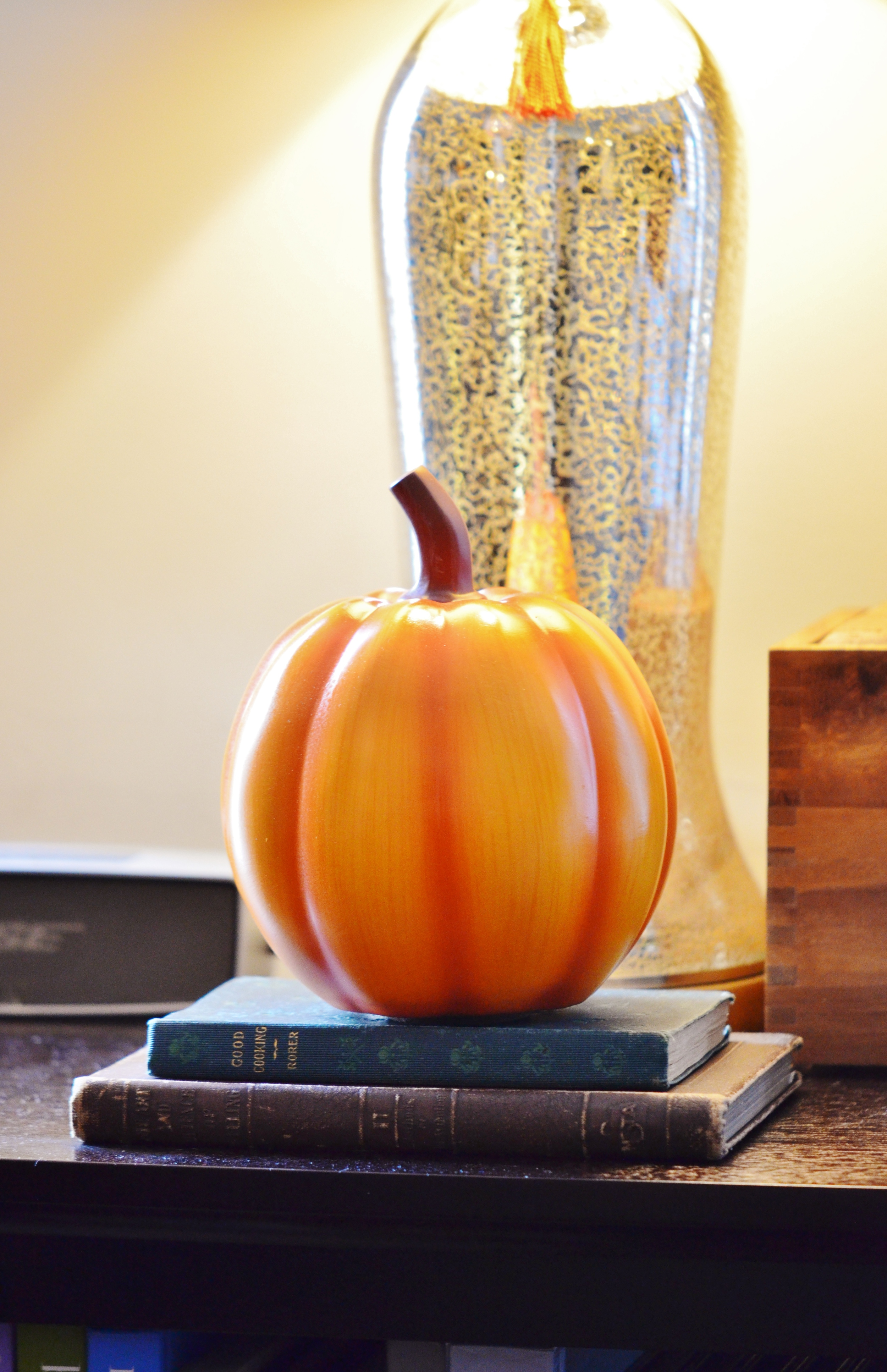 Another simple pumpkin set atop a small pile of antique cookbooks on a side table in the dining room.  Small pops of color throughout a space will keep the flow of your theme consistant without being overpowering.