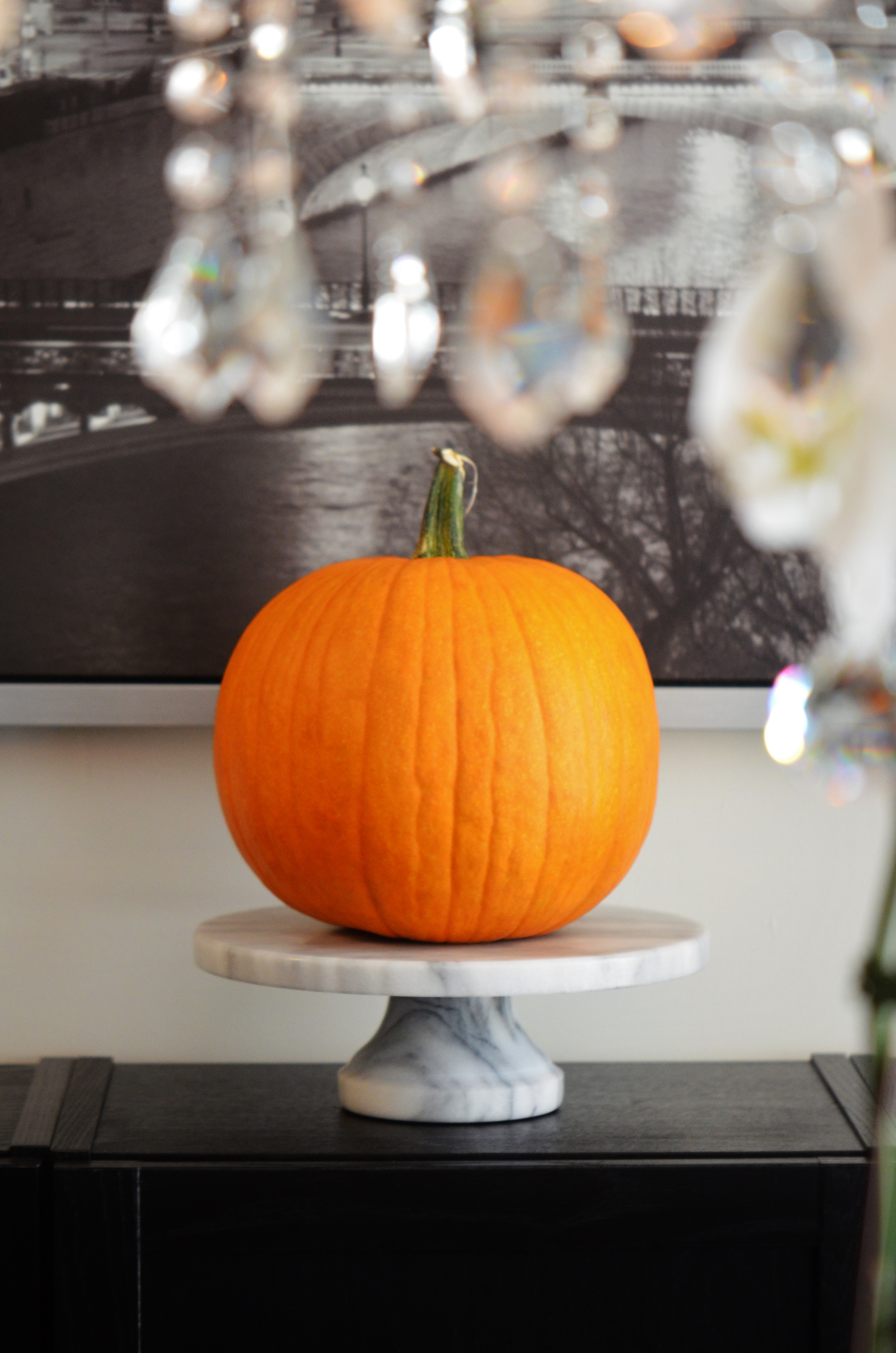 Make a bold and refined statement with a single pumpkin on a pedestal.  This look adds sophistication to the simplest of elements and looks fabulous on a sideboard, coffee table, dinning table, or entry table.  If you have multiple pedestals in varying sizes, create an entire display using different sized pumpkins, gourds, and candles.