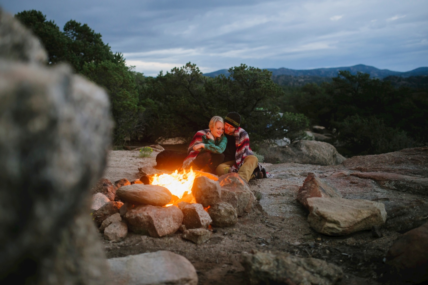 Adorable camping engagement photoshoot cuddling by the fire // Maddie Mae Photography // Epic Adventure Colorado Engagement Photographer