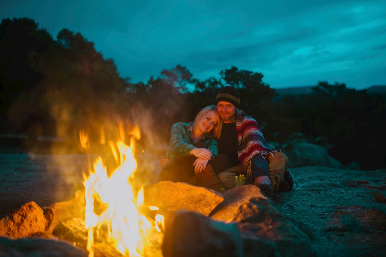 Adorable camping photo shoot with a couple cuddling by a fire // Bonfire engagement photos // Maddie Mae Photography