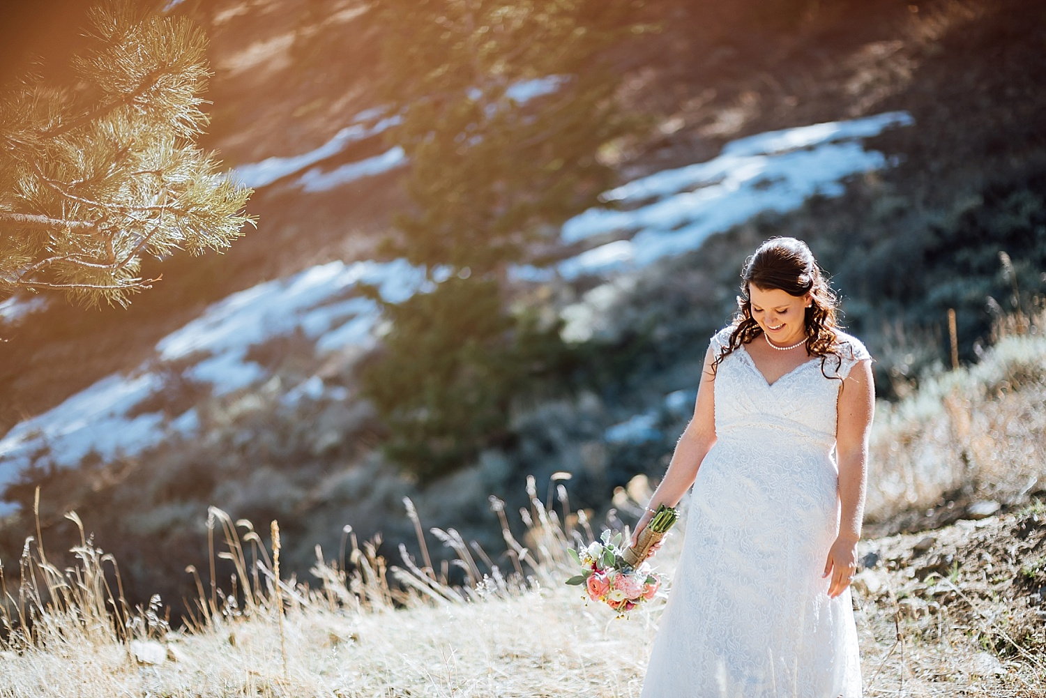This bride looks so happy! I love how she paired the pearl necklace with the lace dress. Also, how fun would it be to have your wedding photos taken on a mountain with snow in the background!Photo by Maddie Mae Photography