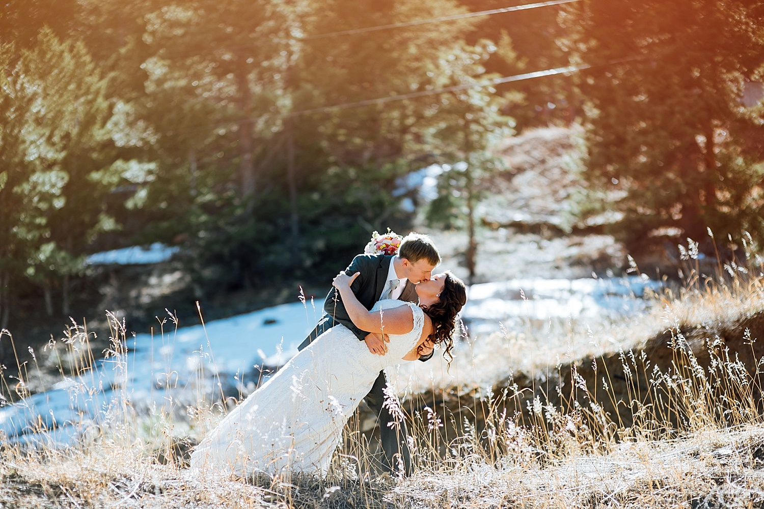 This dip kiss pose is so cute with the sunlight like that. Mary's Lake Lodge is an incredible wedding venue- especially with snow still on the mountains up in Estes Park!Photo by Maddie Mae Photography